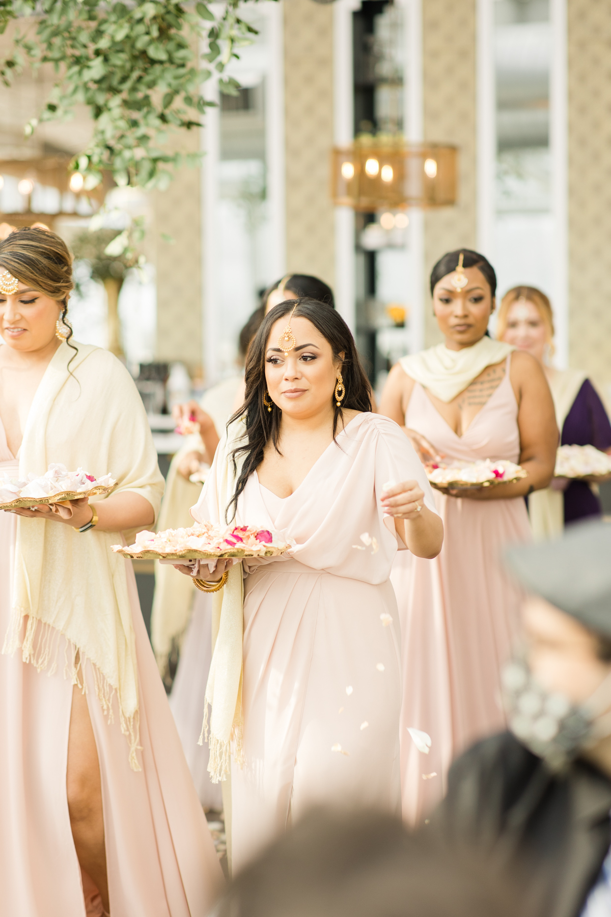 bridesmaids dropping petals from gold trays during wedding ceremony processional