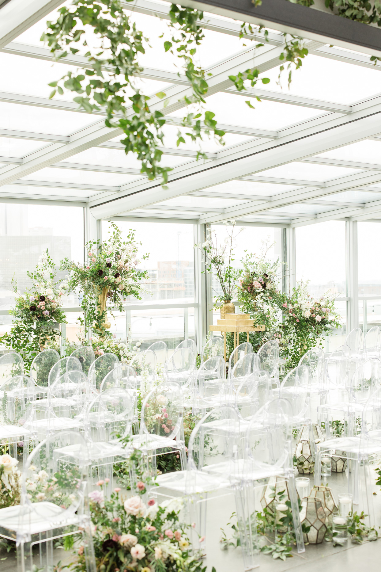elegant ceremony set up with florals and clear chairs