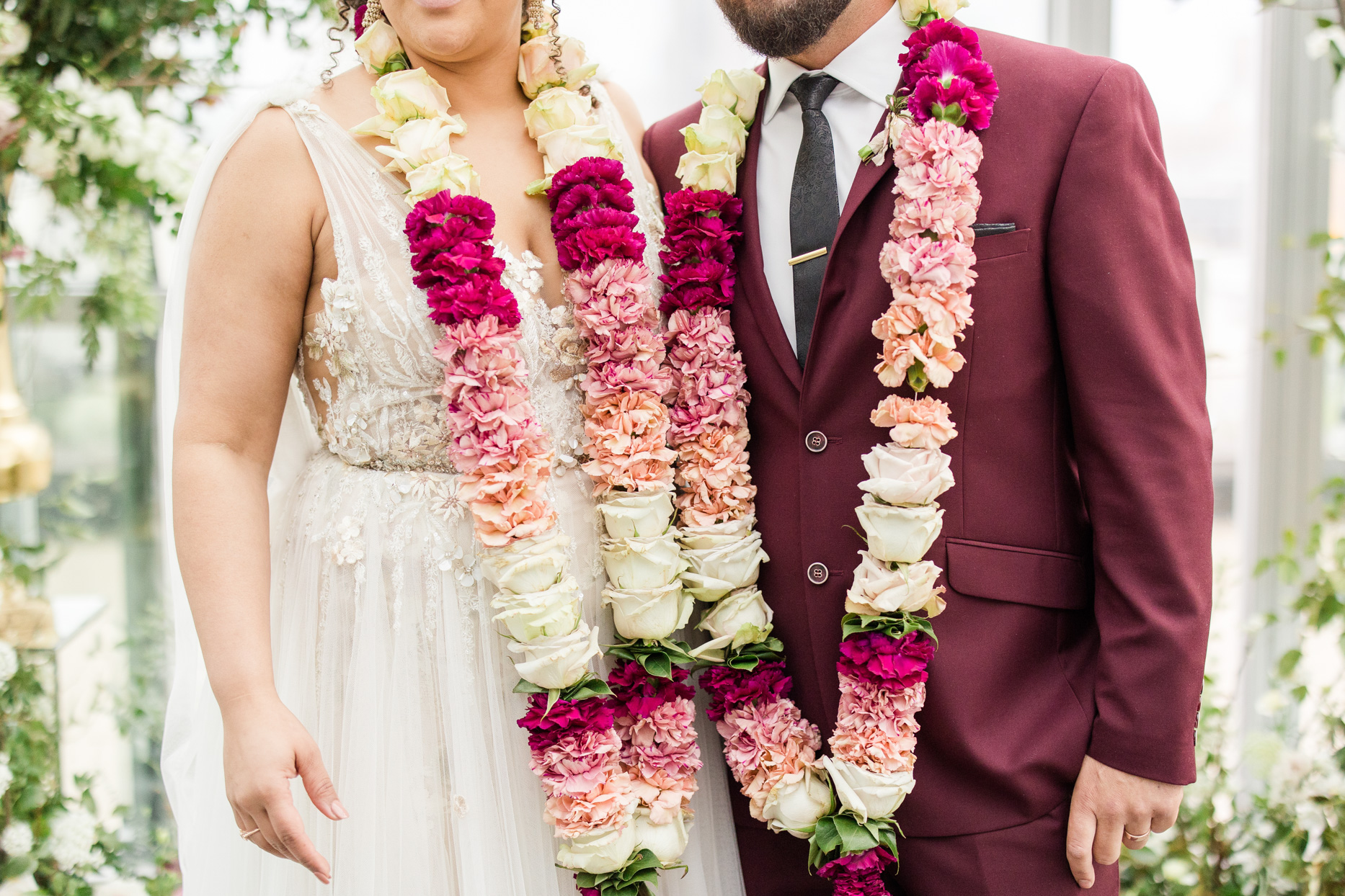 bride and groom wearing pink and white floral garlands