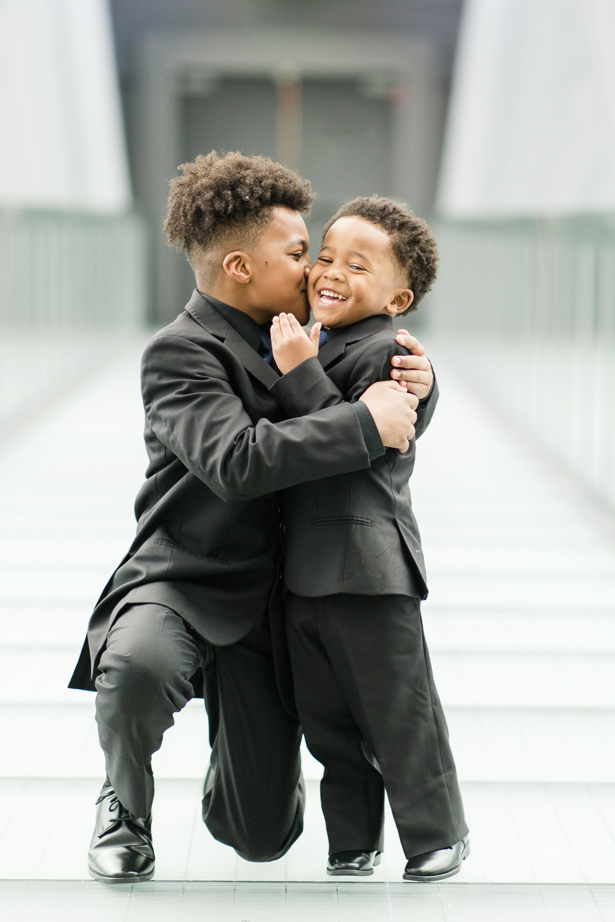ring bearers in black suits hugging and smiling