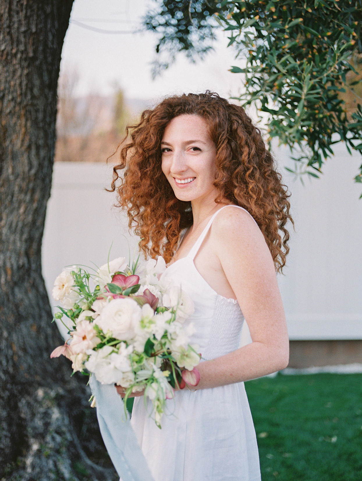 bride in simple white dress holding white and pink floral bouquet