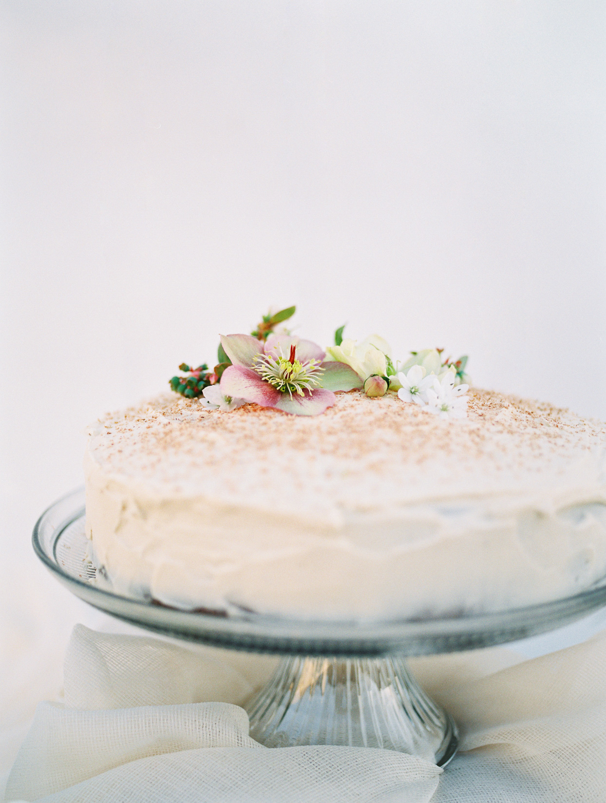 simple single layer wedding cake with crumb topping and flowers