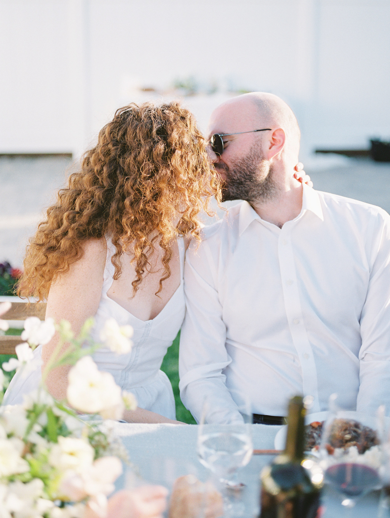 couple in white kissing at reception table