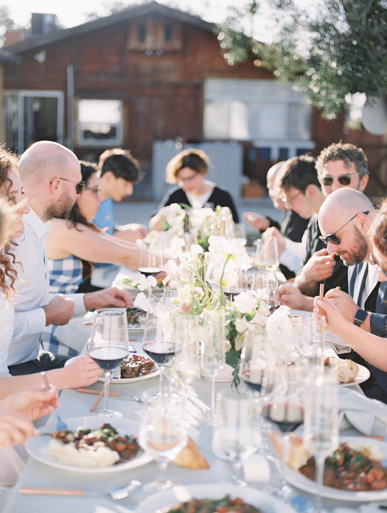 wedding guests sitting at outdoor table eating dinner