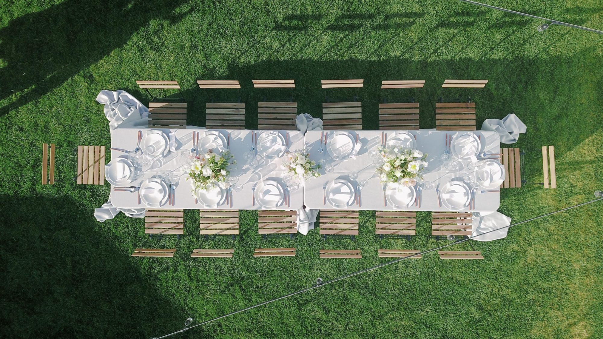 overhead view of long white table for lawn reception