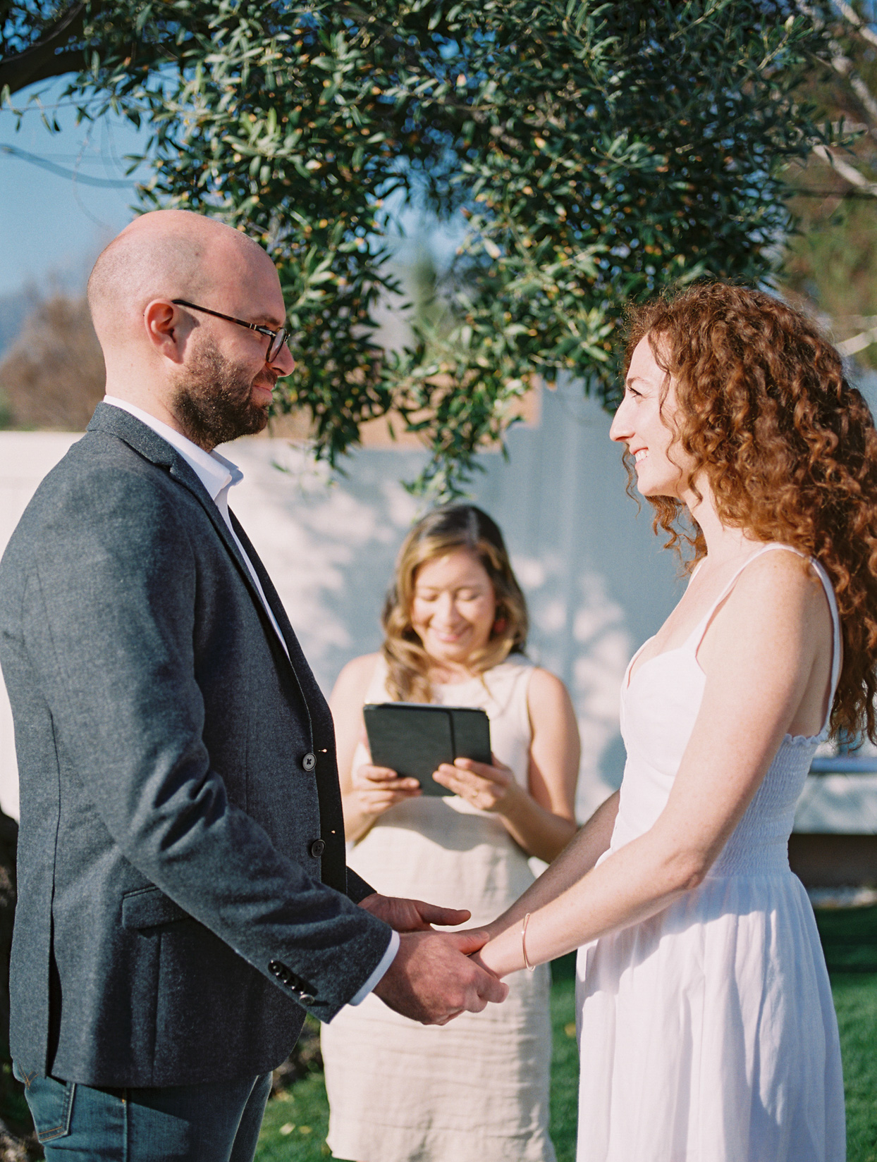 couple holding hands for wedding vows in backyard ceremony