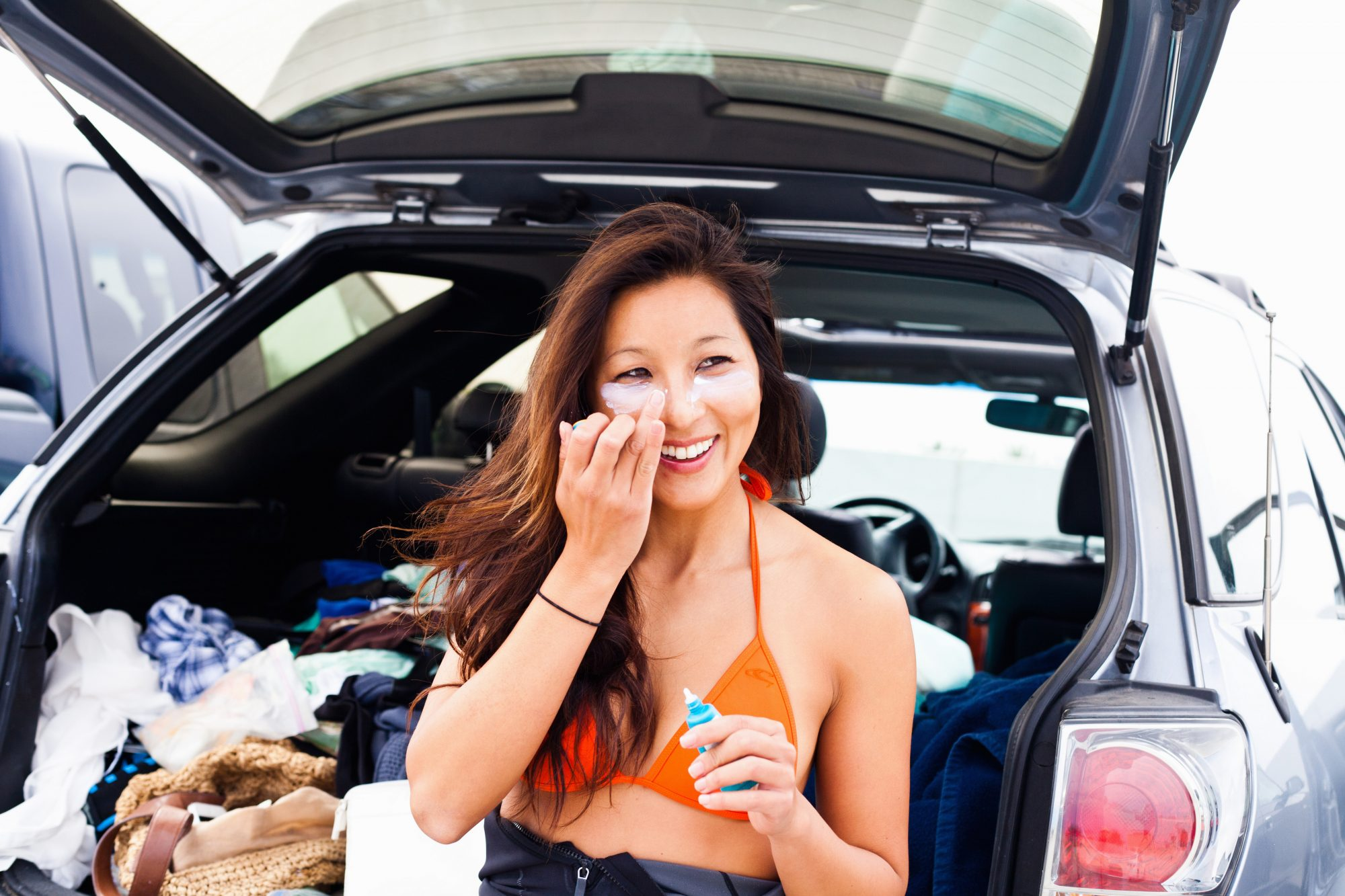 woman applying sunscreen to face sitting back of car