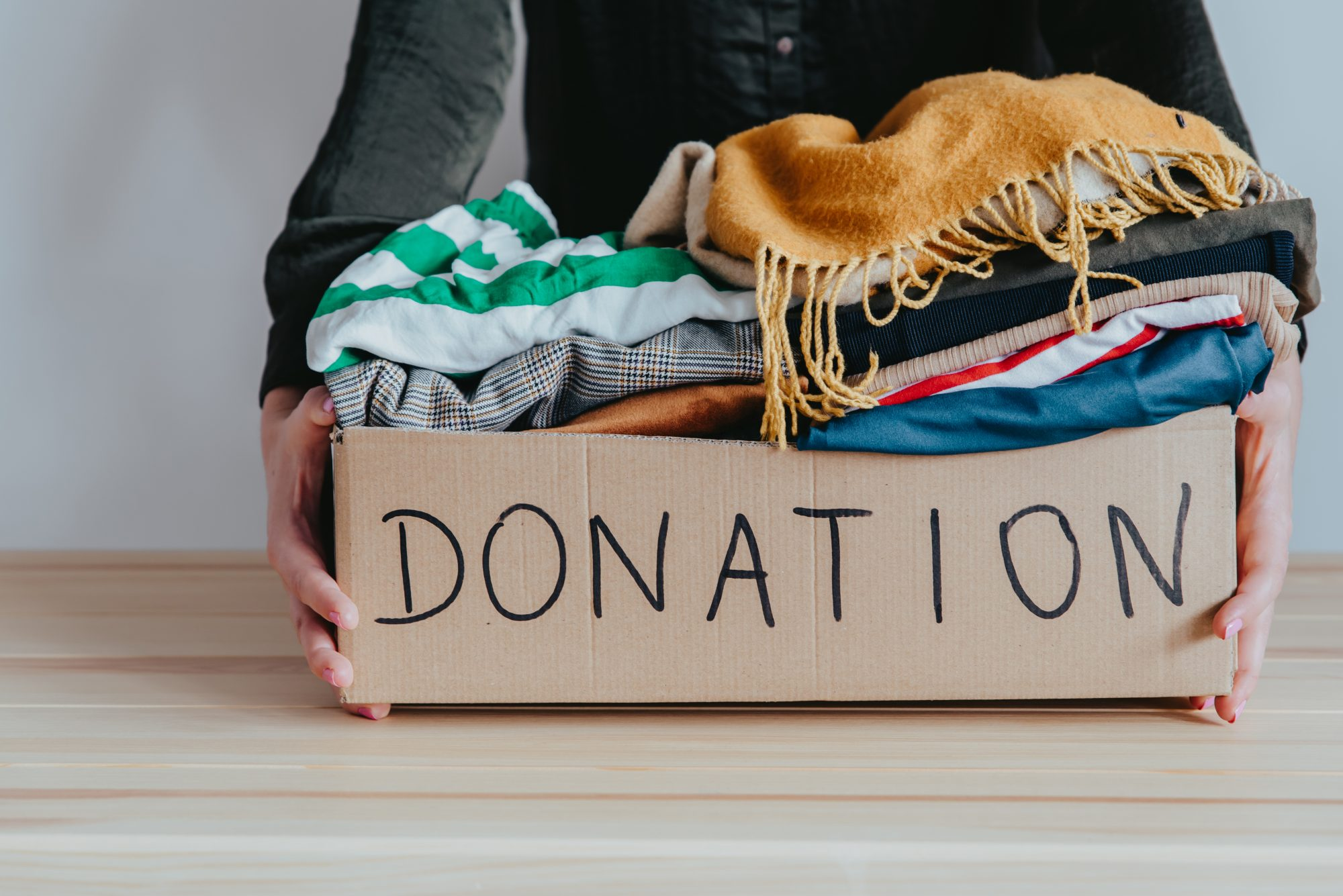 Woman holding cardboard donation box full with folded clothes