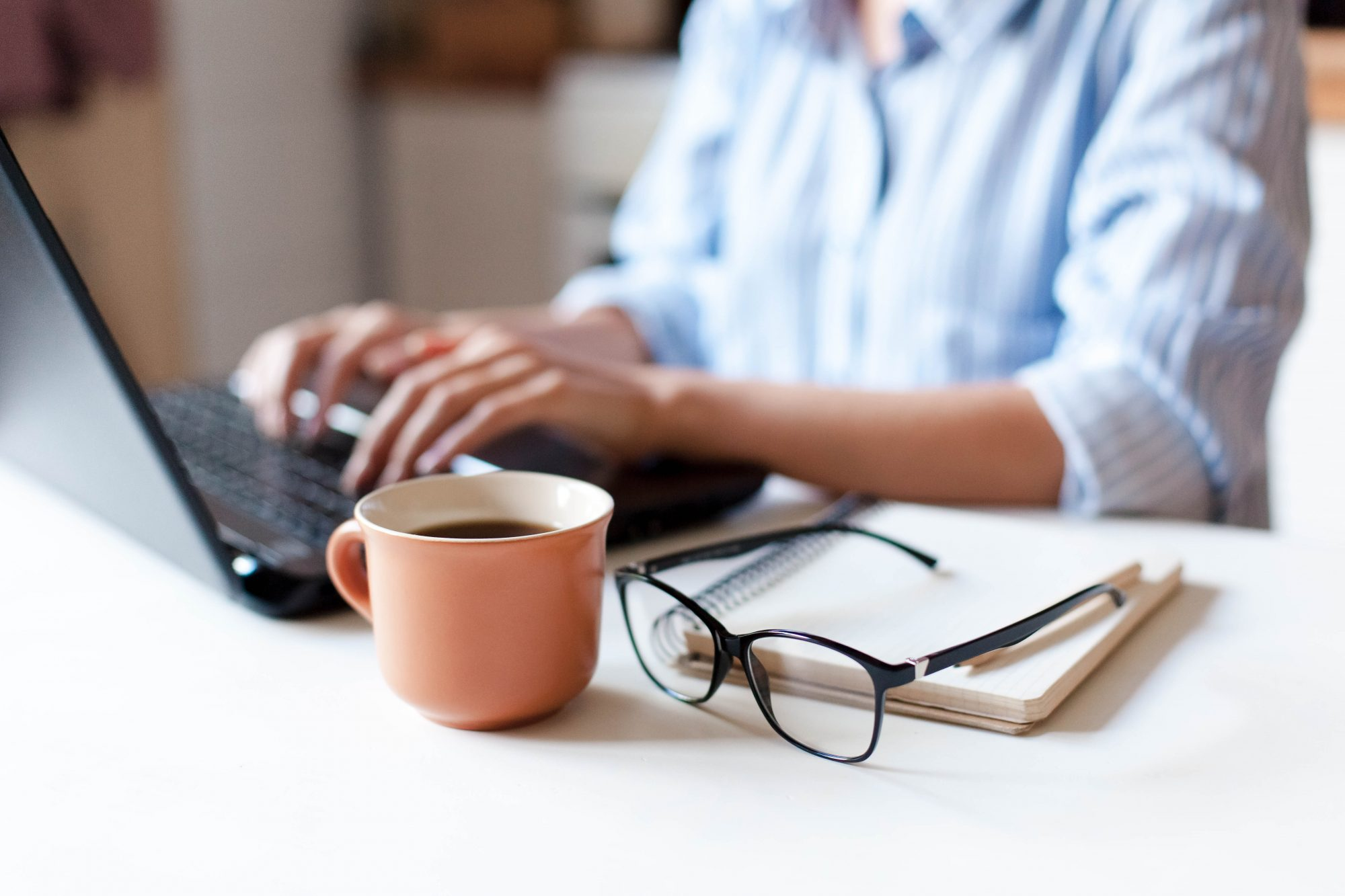 woman working on laptop with coffee cup