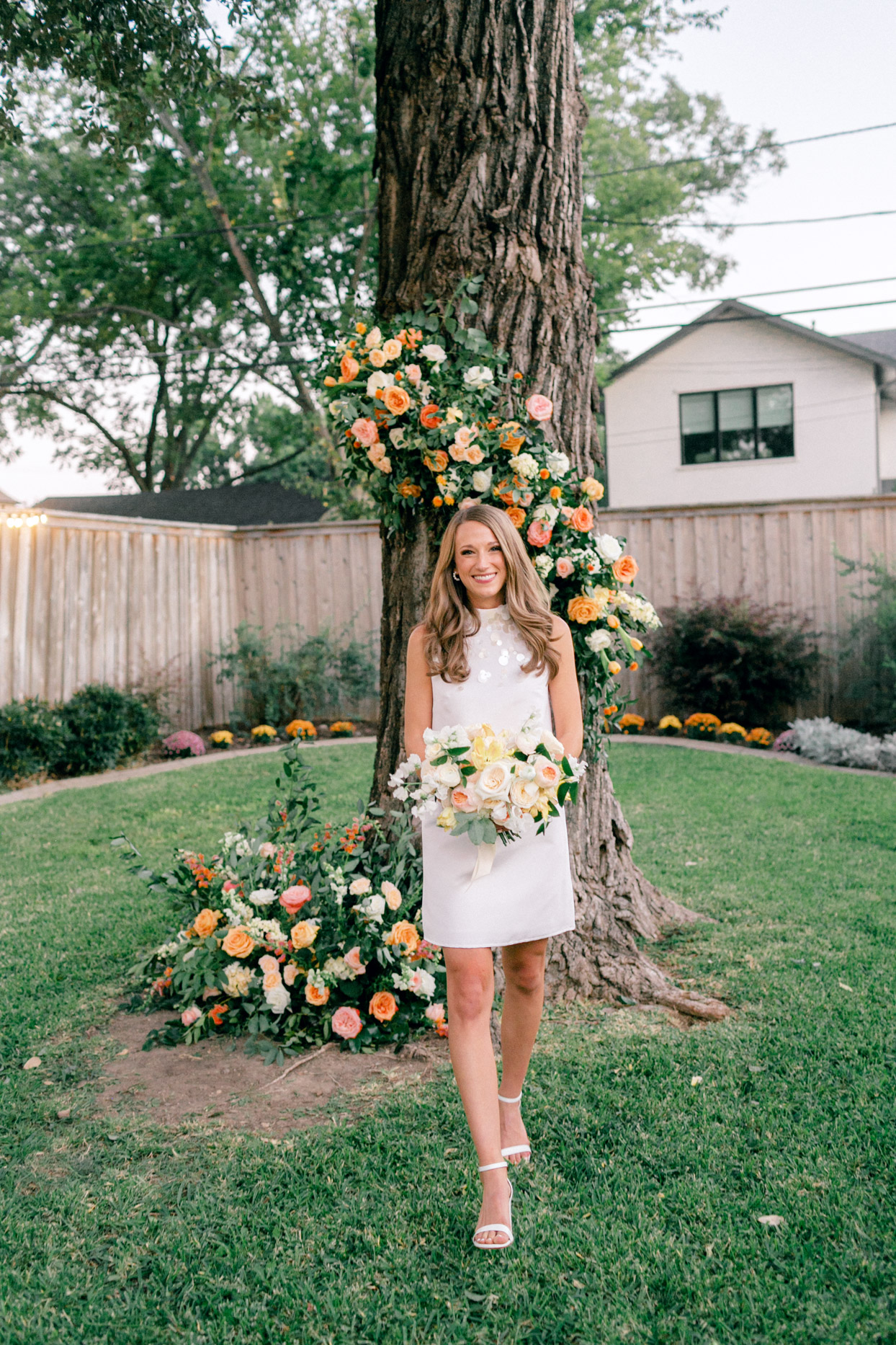 bride in short white dress holding orange, yellow and white flowers