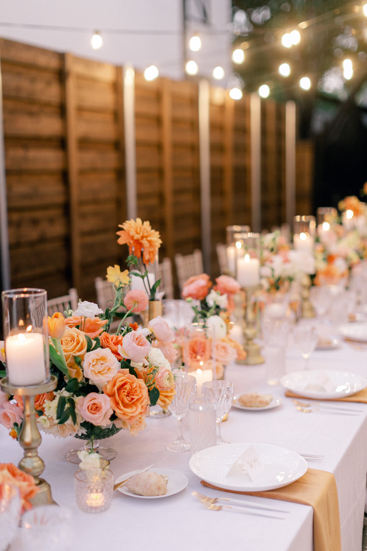 long white wedding table with orange and yellow flowers and decorations