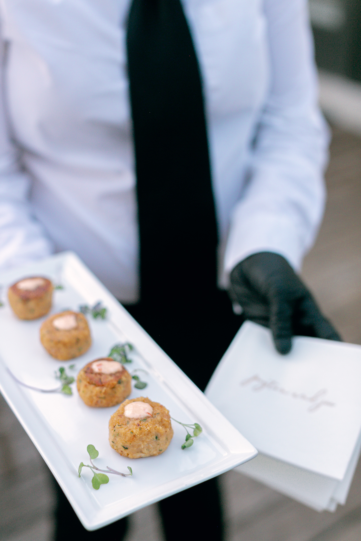 person holding white tray of wedding appetizers