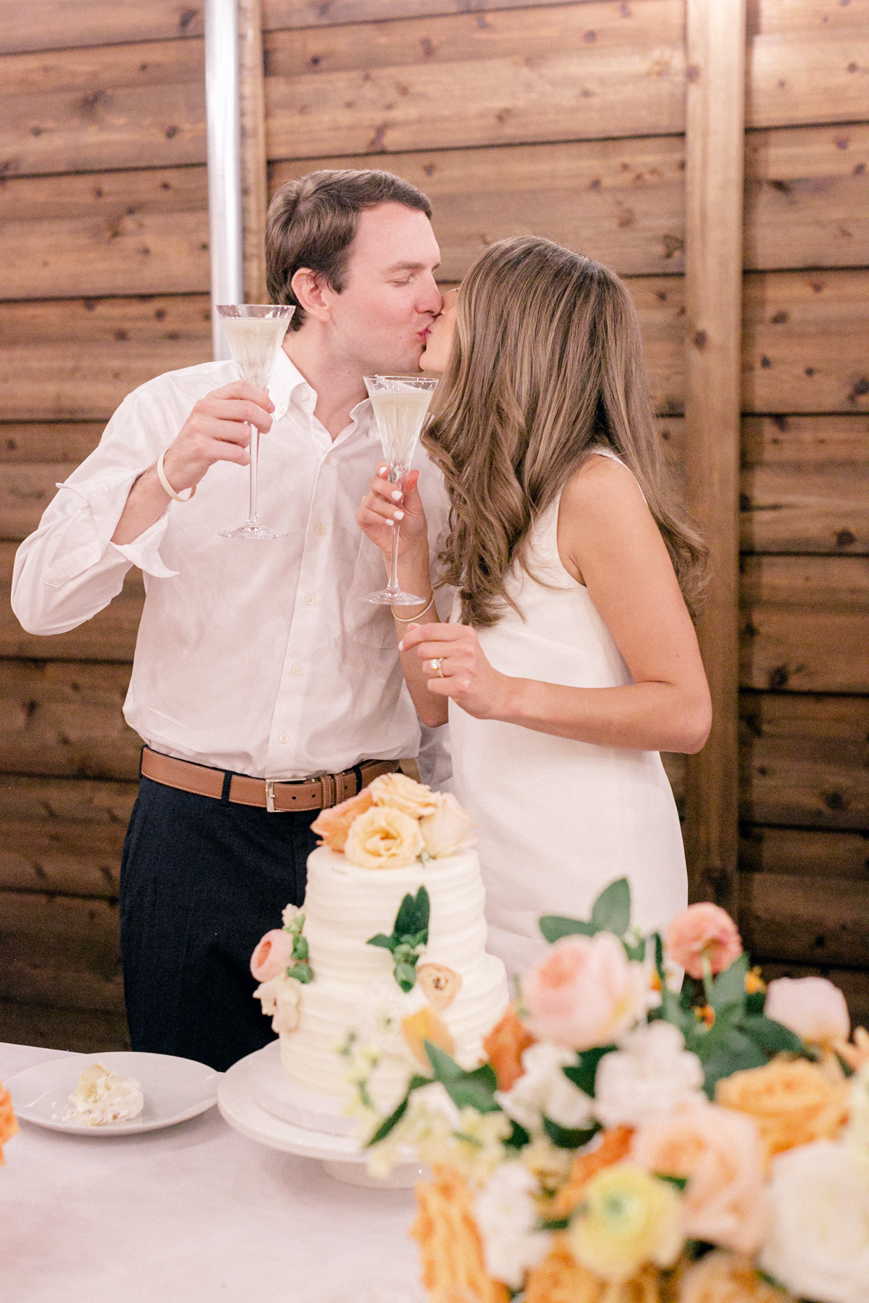 couple kissing with champagne and wedding cake
