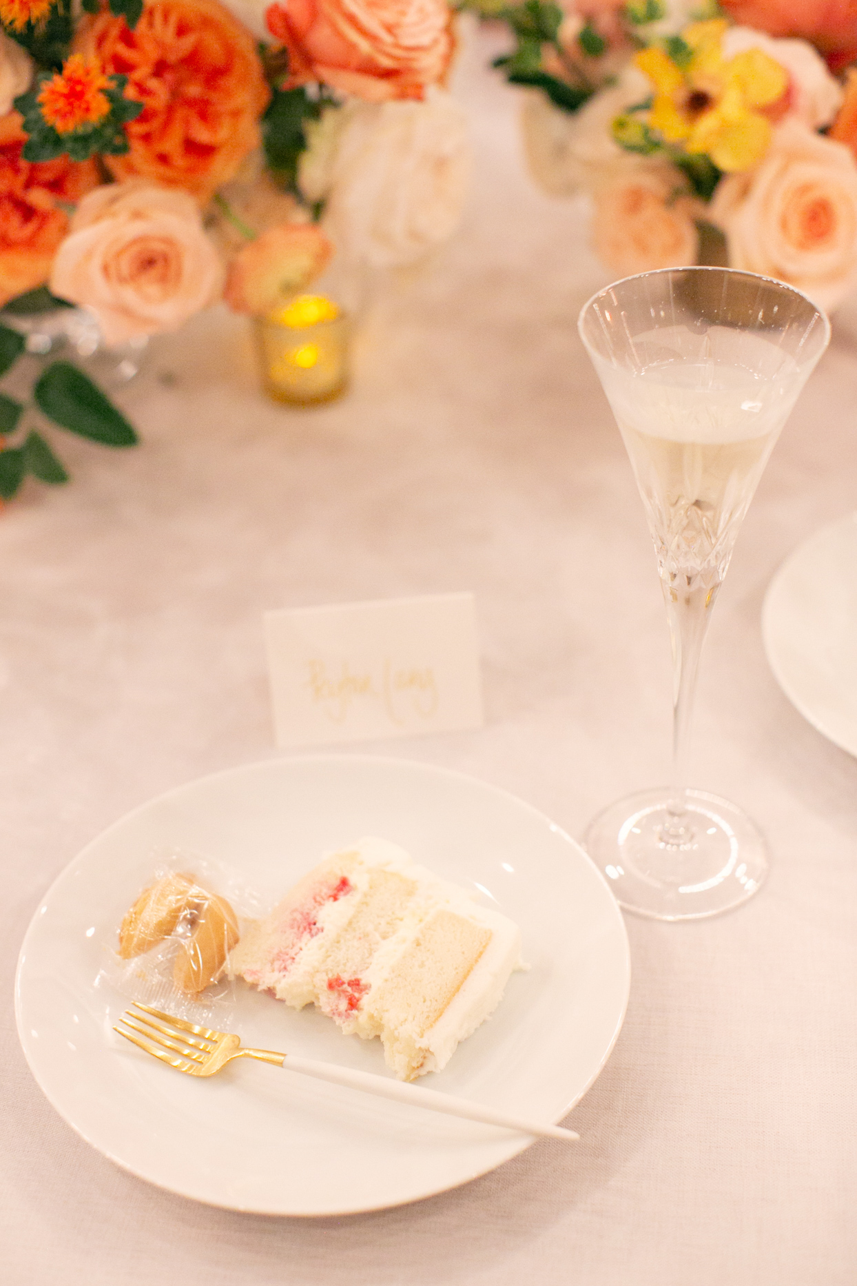 slice of cake and fortune cookie on plate at wedding reception