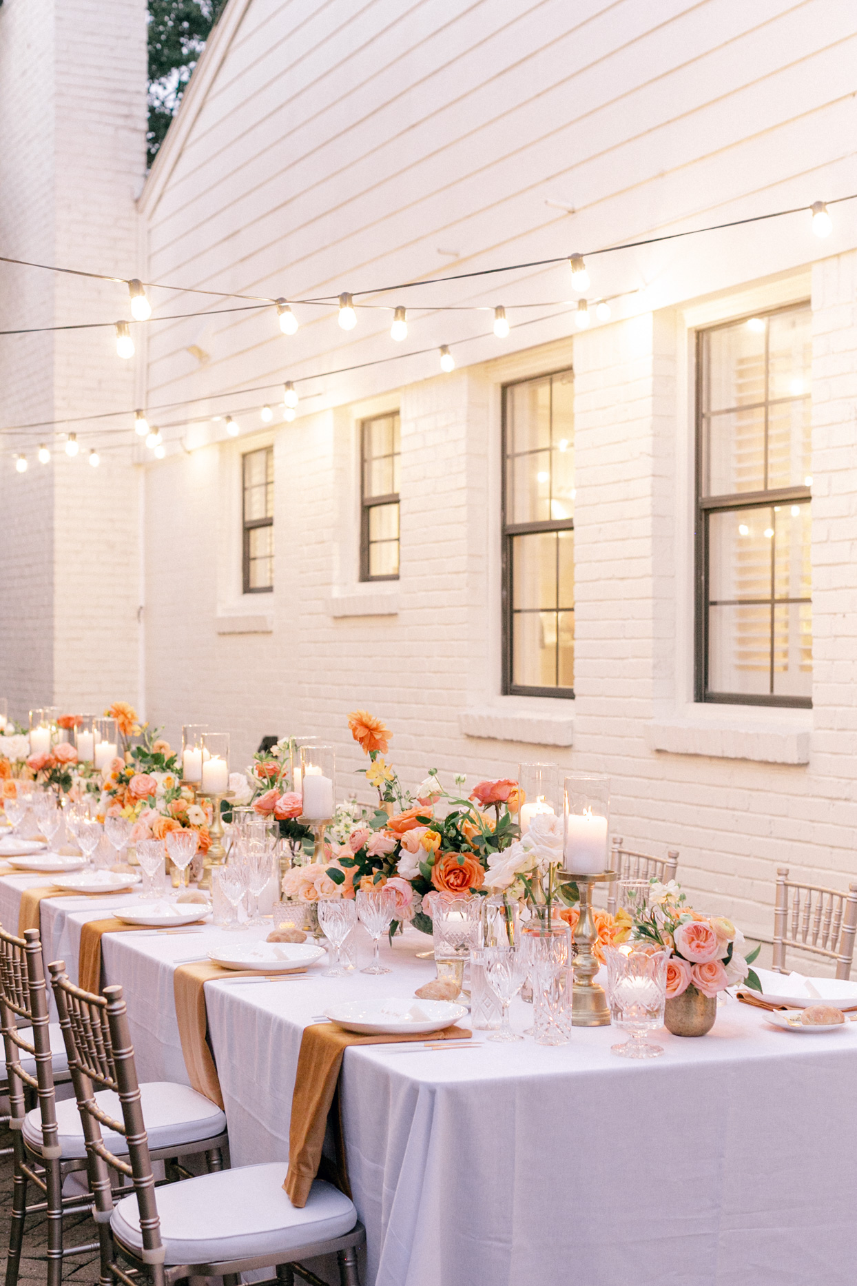 wedding reception table set up on side of house with string lights above
