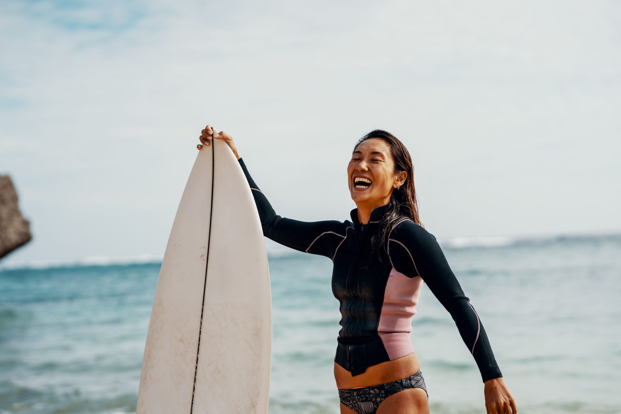 smiling woman at beach with surfboard