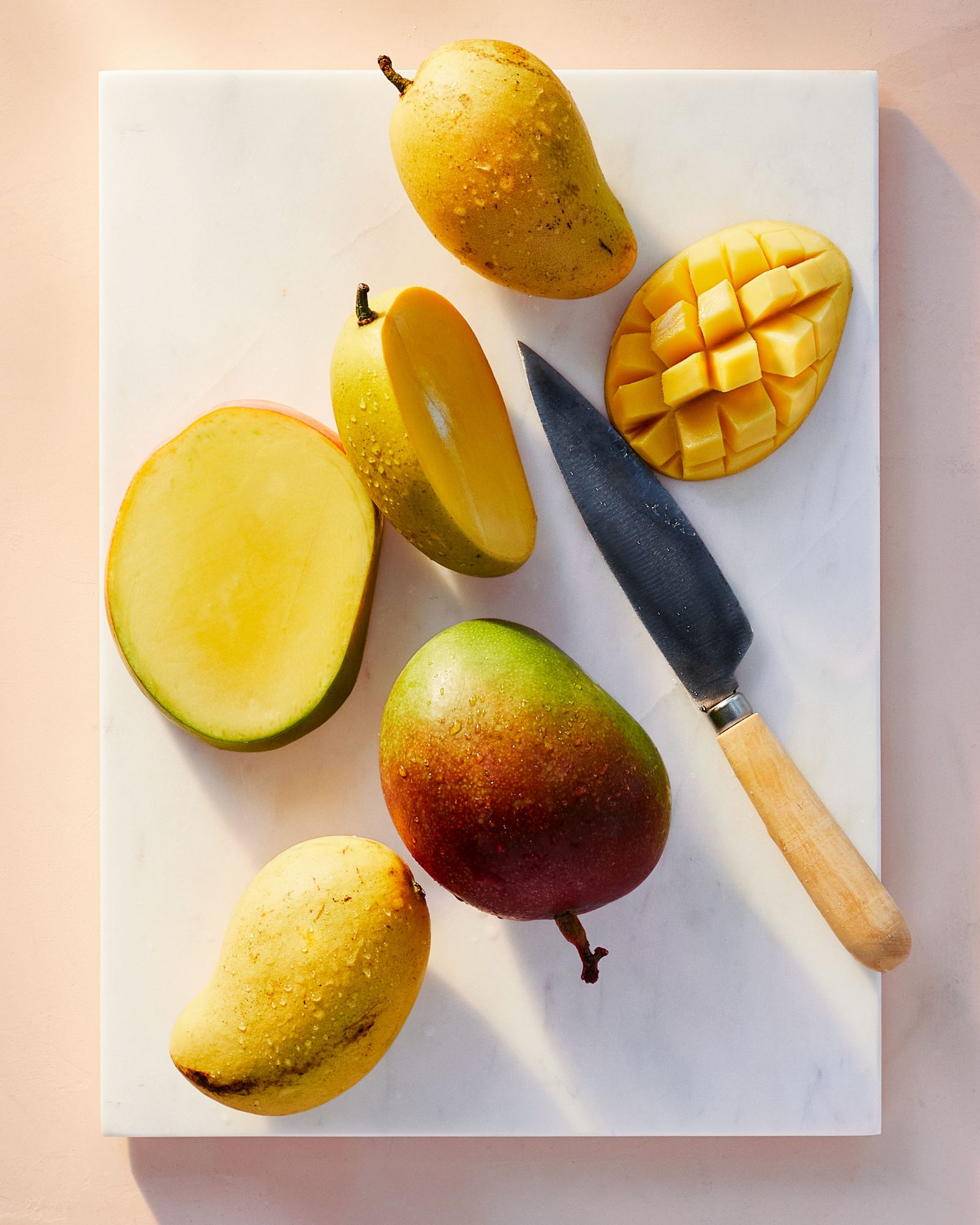 sliced mangoes on cutting board with knife