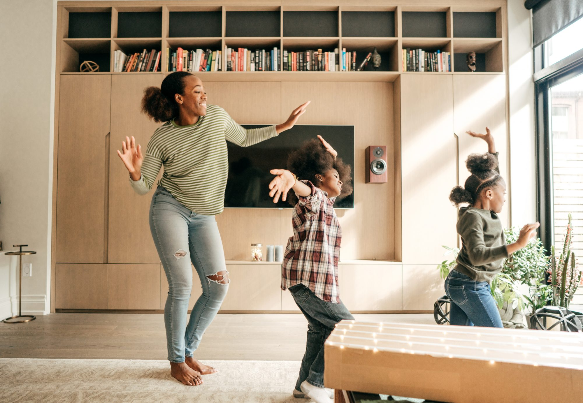 mother and two daughters dancing living room
