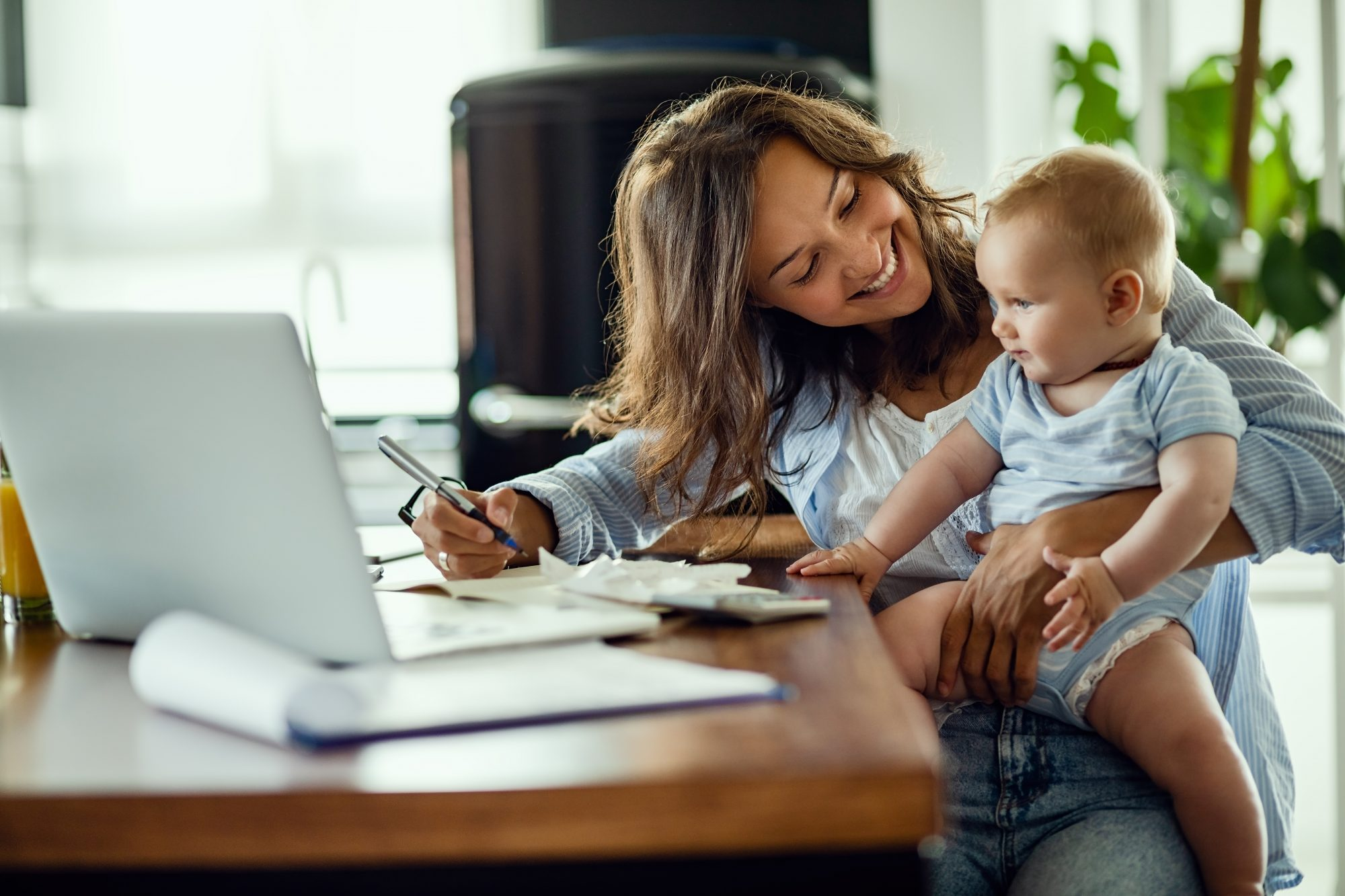 woman calculating finances at table with baby on lap