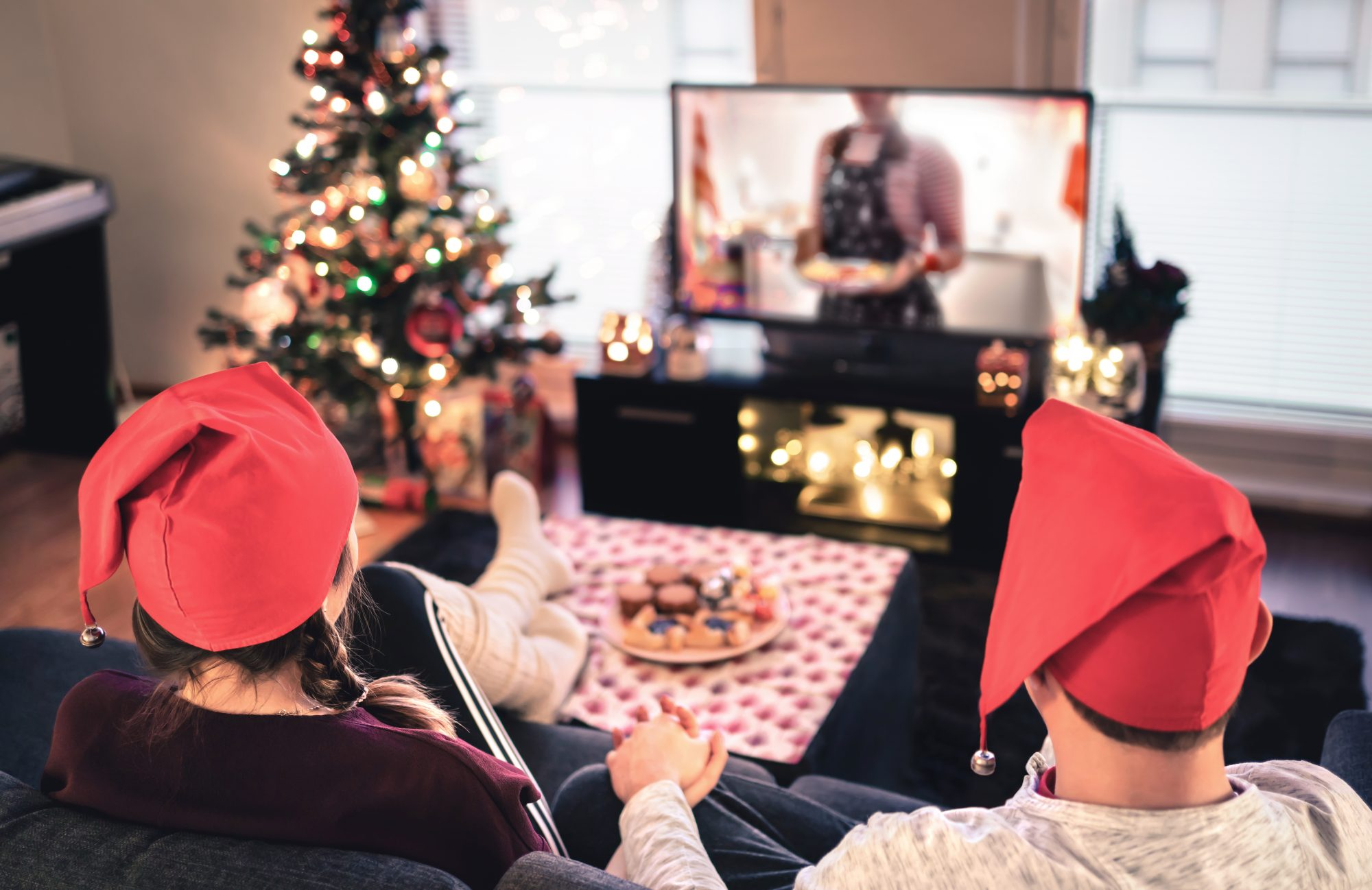 couple watching holiday movie with treats