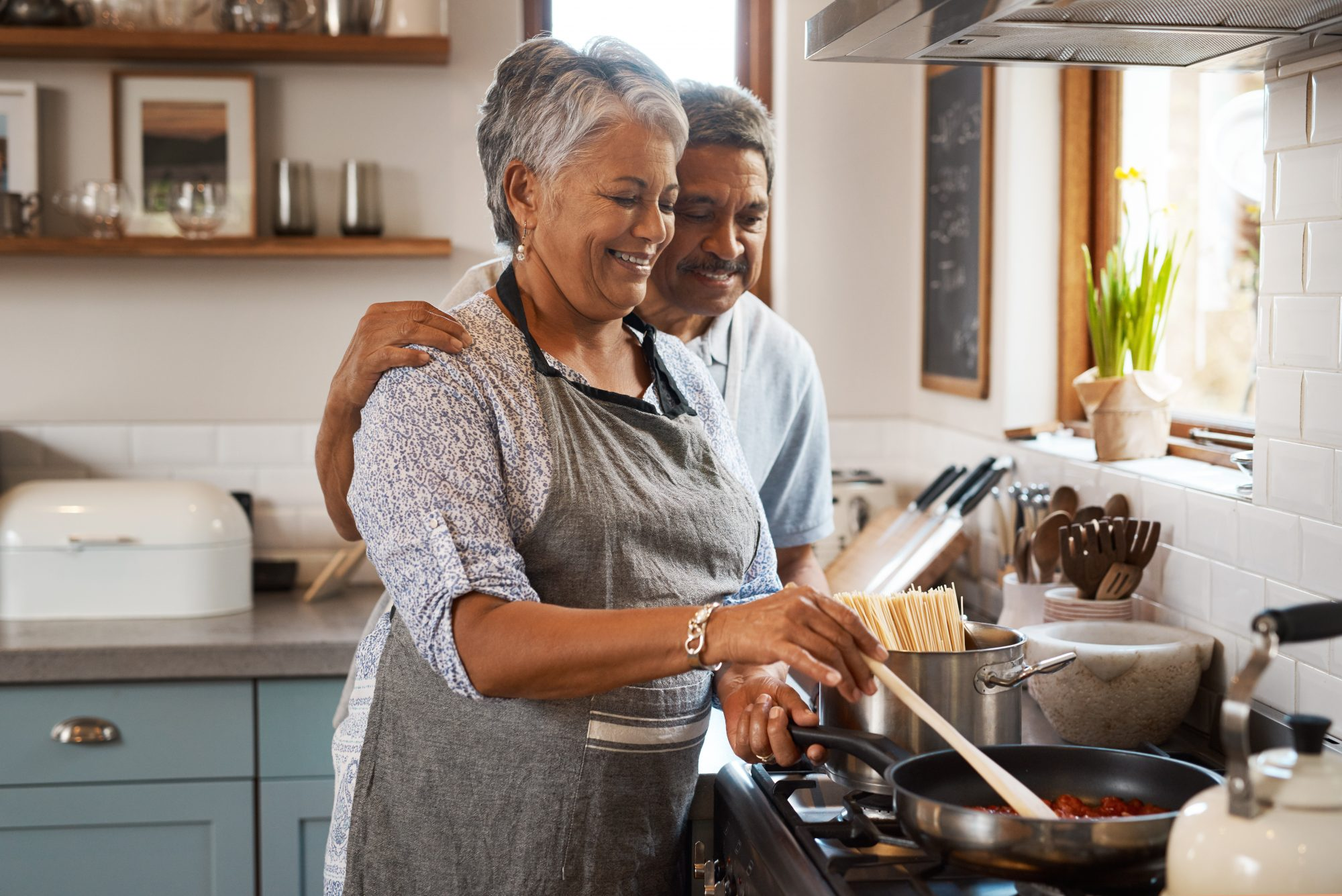 mature couple cooking bolognese on the stove