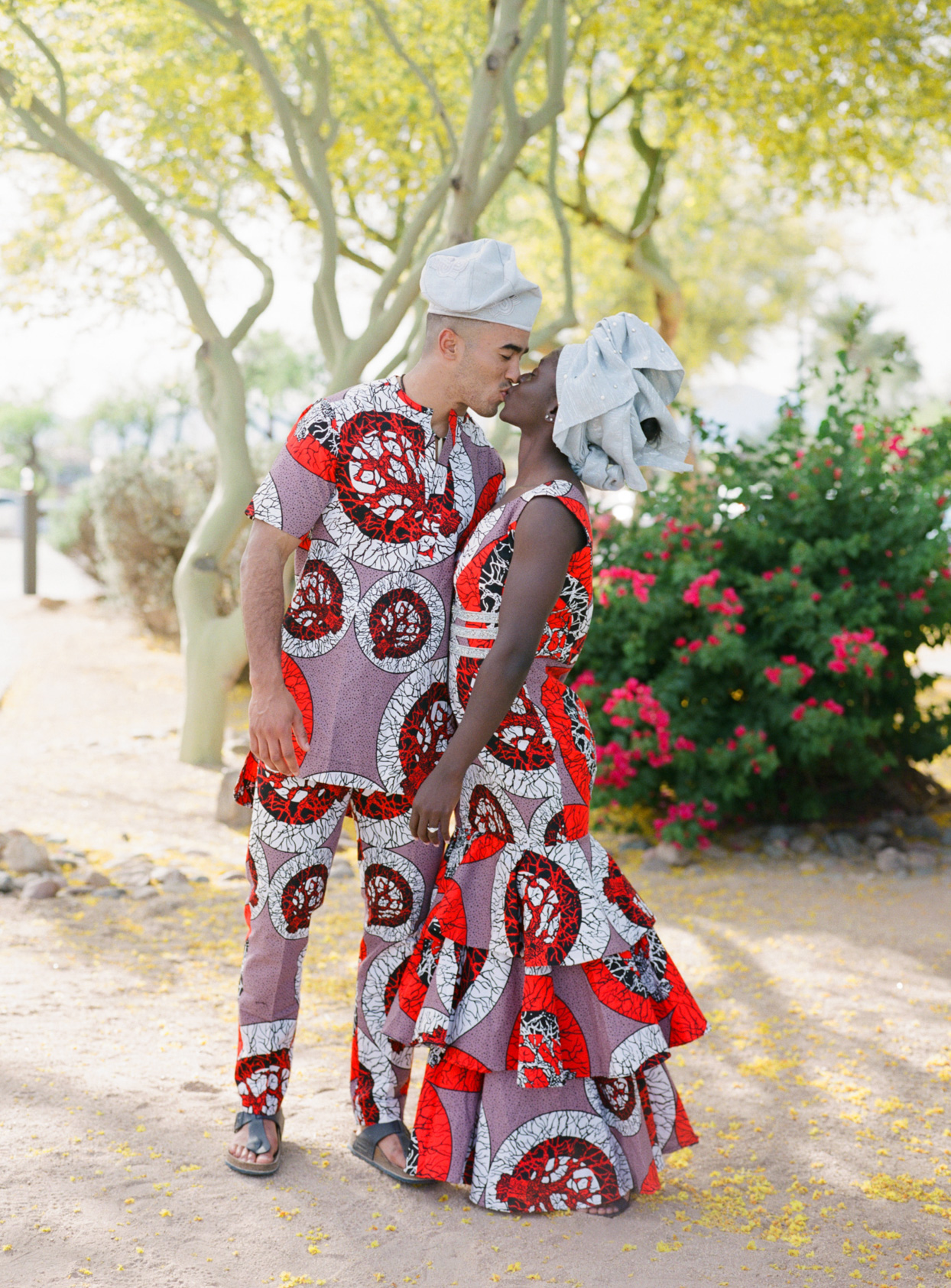 couple kissing at rehearsal dinner in traditional african attire