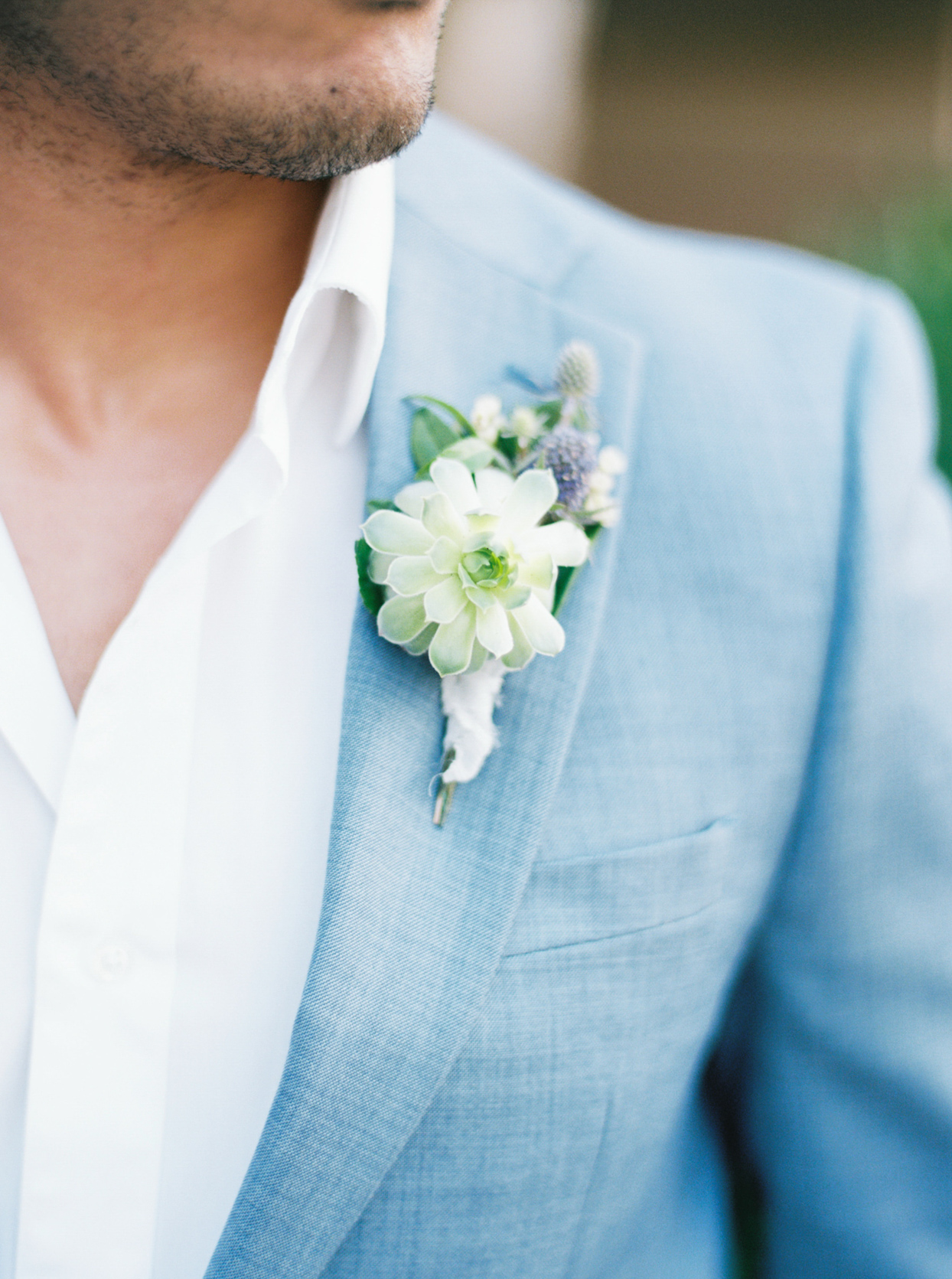 white boutonniere on groom's light blue suit