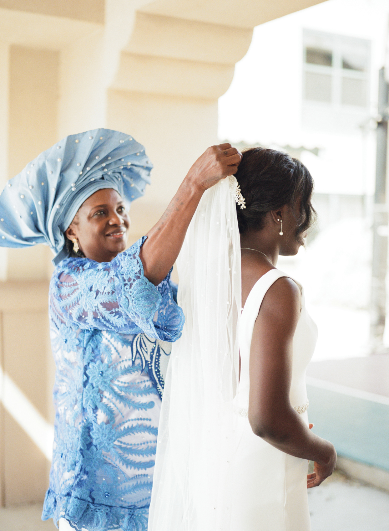 mother in blue helping bride put on veil