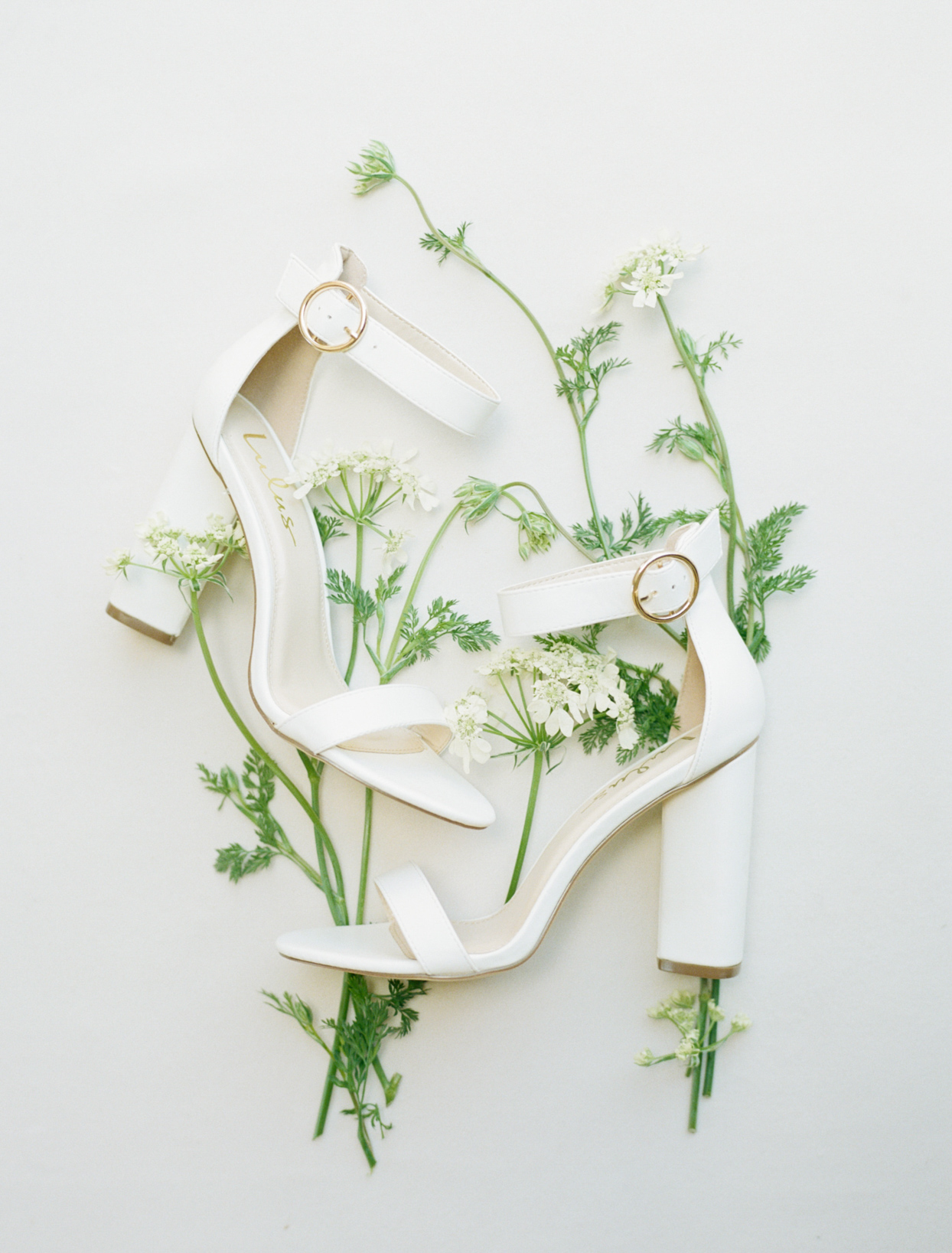 bride's white shoes with herb decorations