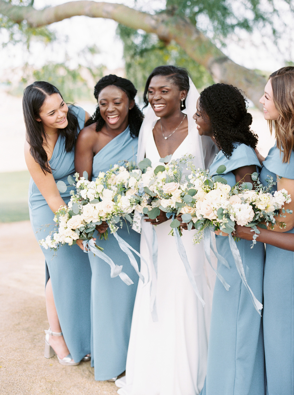 bridesmaids in pale blue dresses with bride