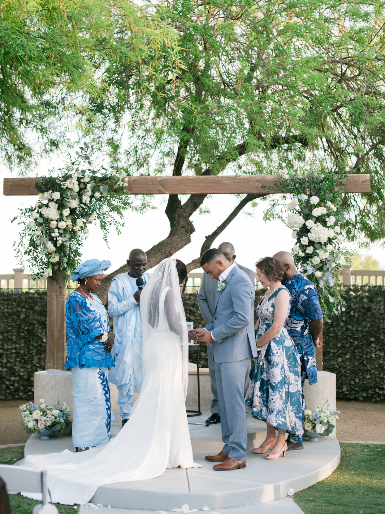 couple praying during wedding ceremony with family