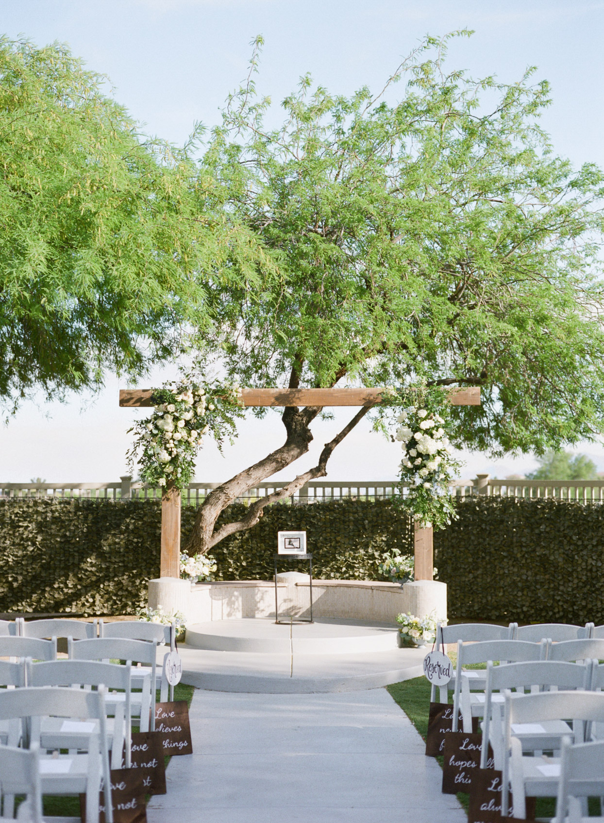 outdoor wedding ceremony set up with wooden arch and white flowers