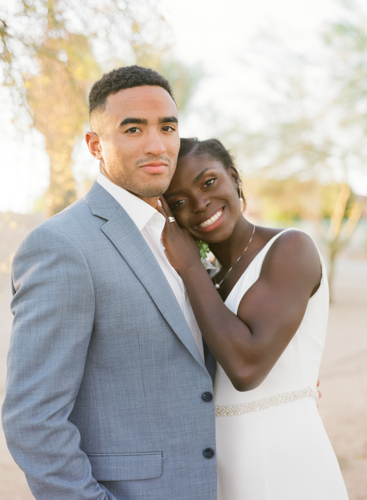 wedding couple portrait with groom in pale blue suit and bride in white