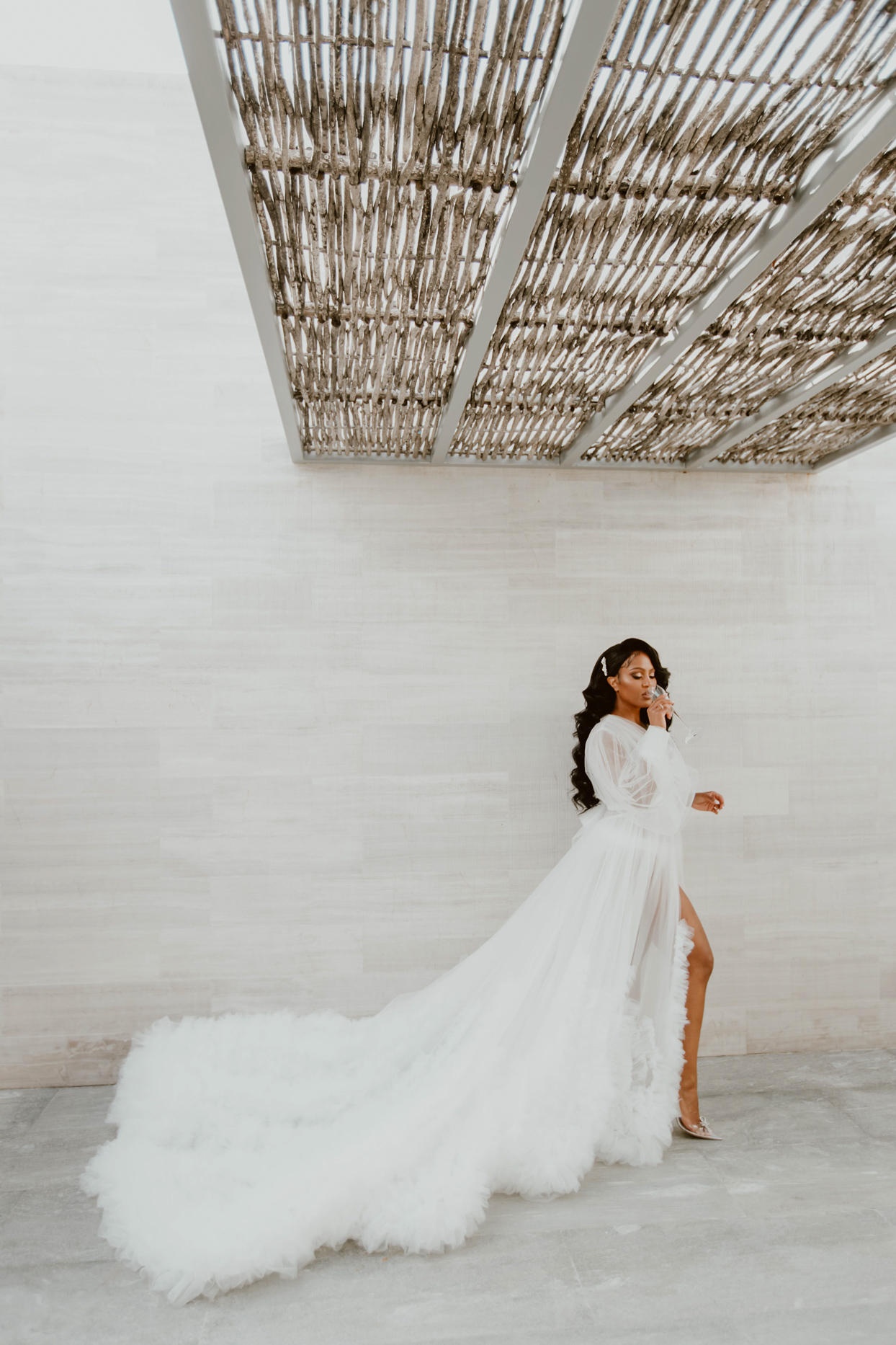 bride drinking champagne in flowing white robe