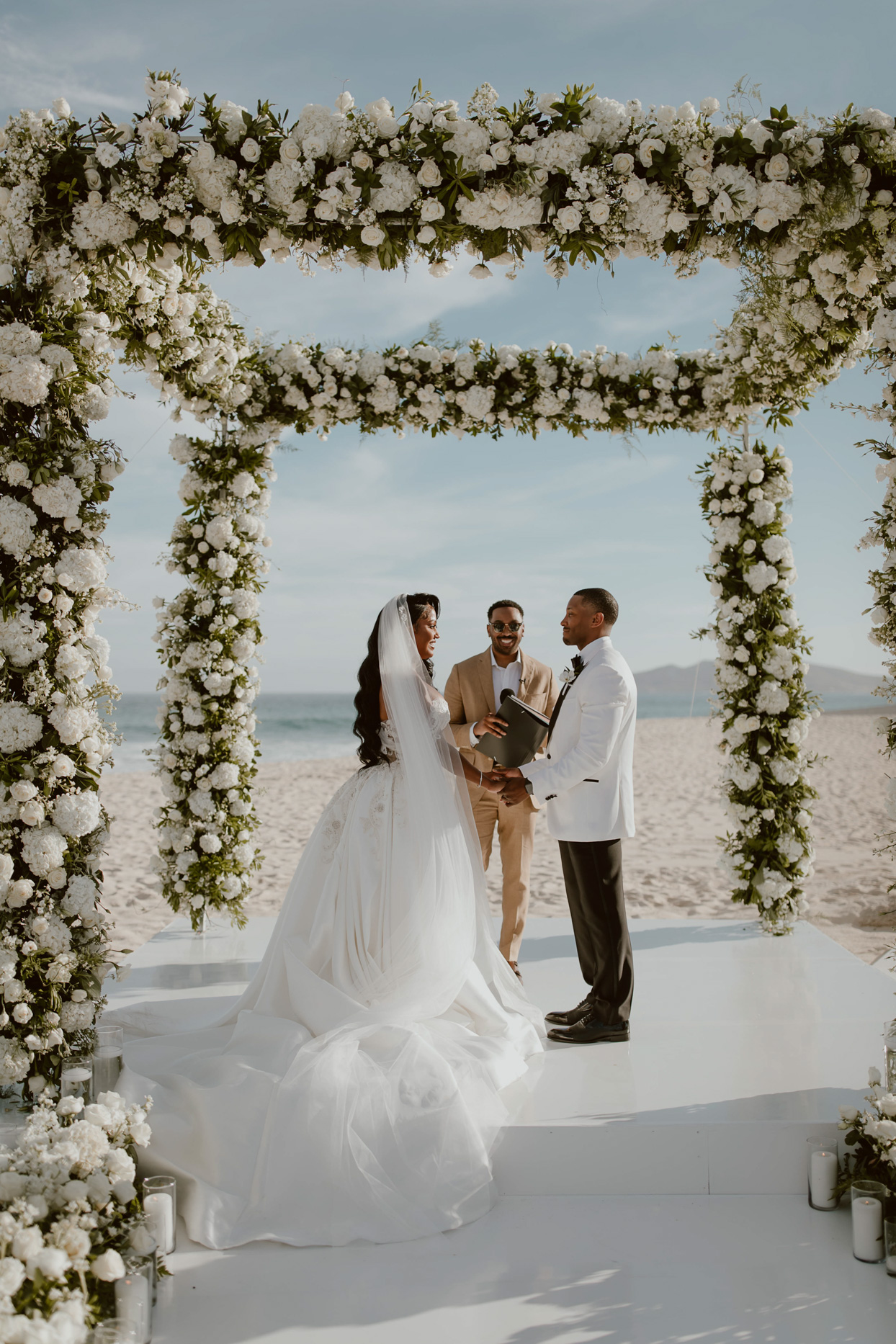 couple during wedding ceremony with white floral arches