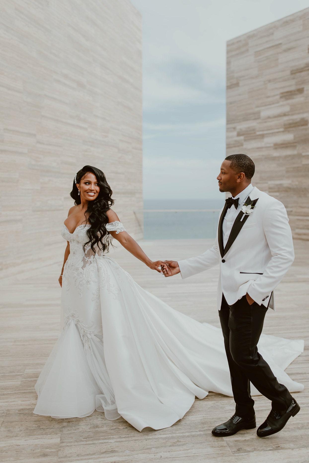bride and groom walking together on modern structure at beach