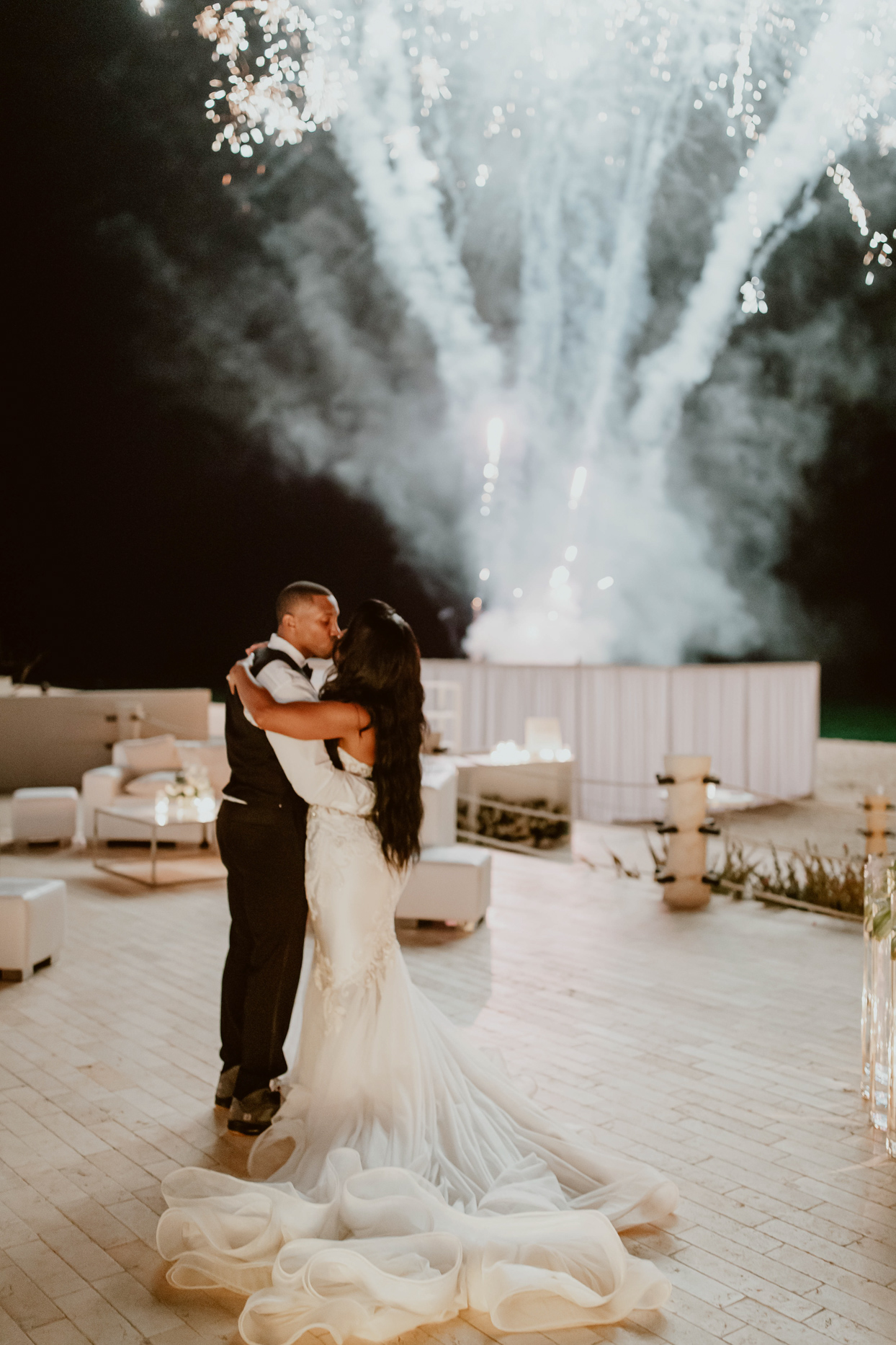couple kissing during wedding fireworks