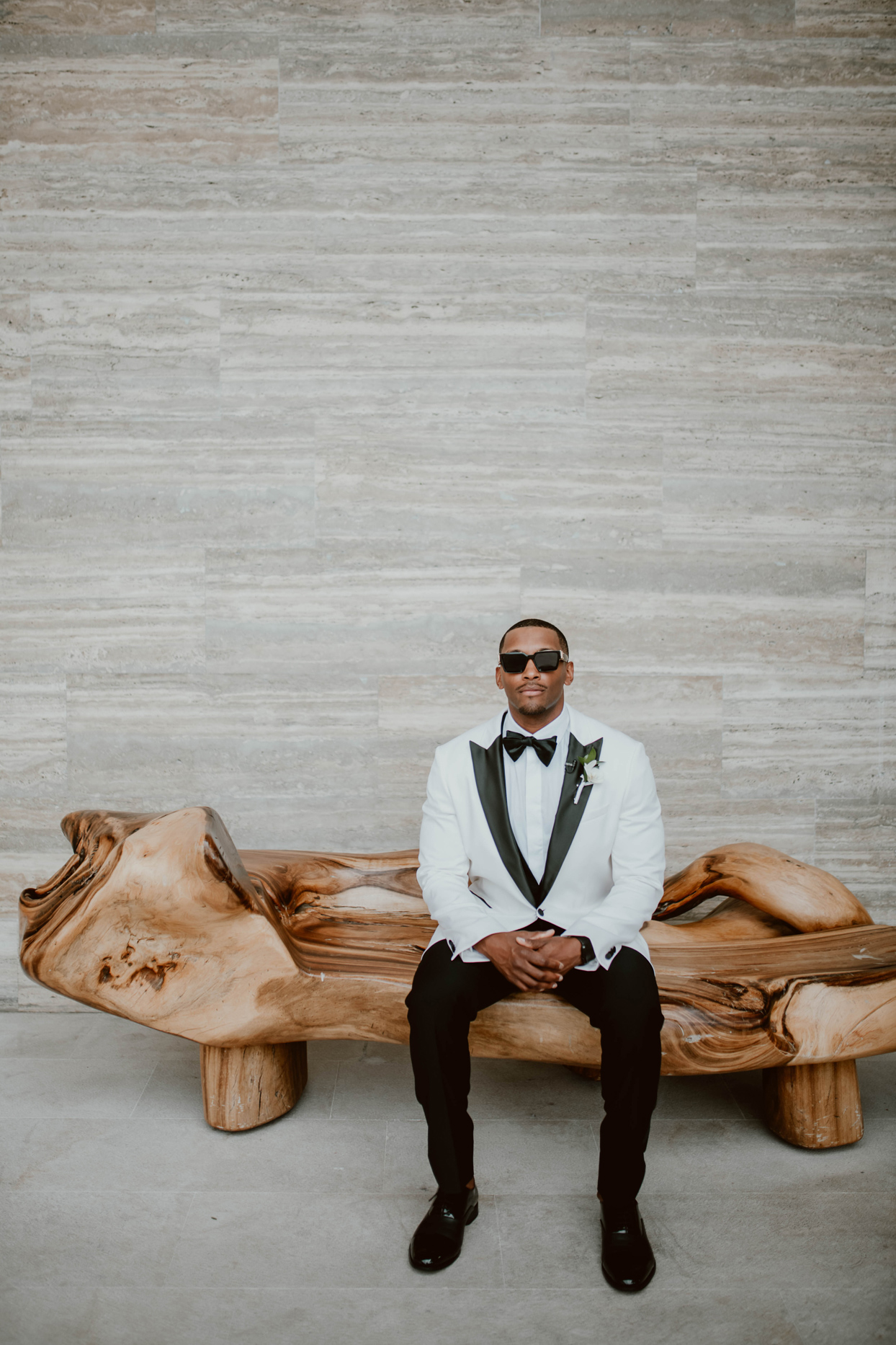 groom in black and white tuxedo sitting on wooden bench