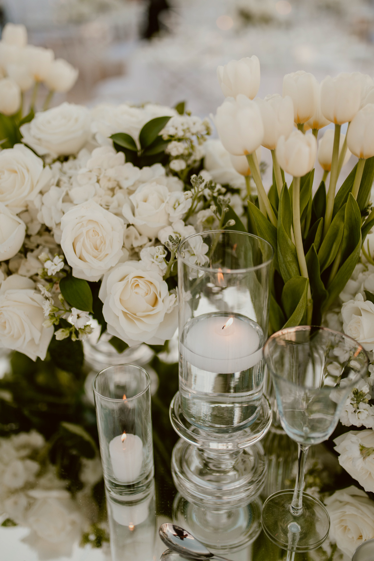 candles and white flowers on wedding reception table
