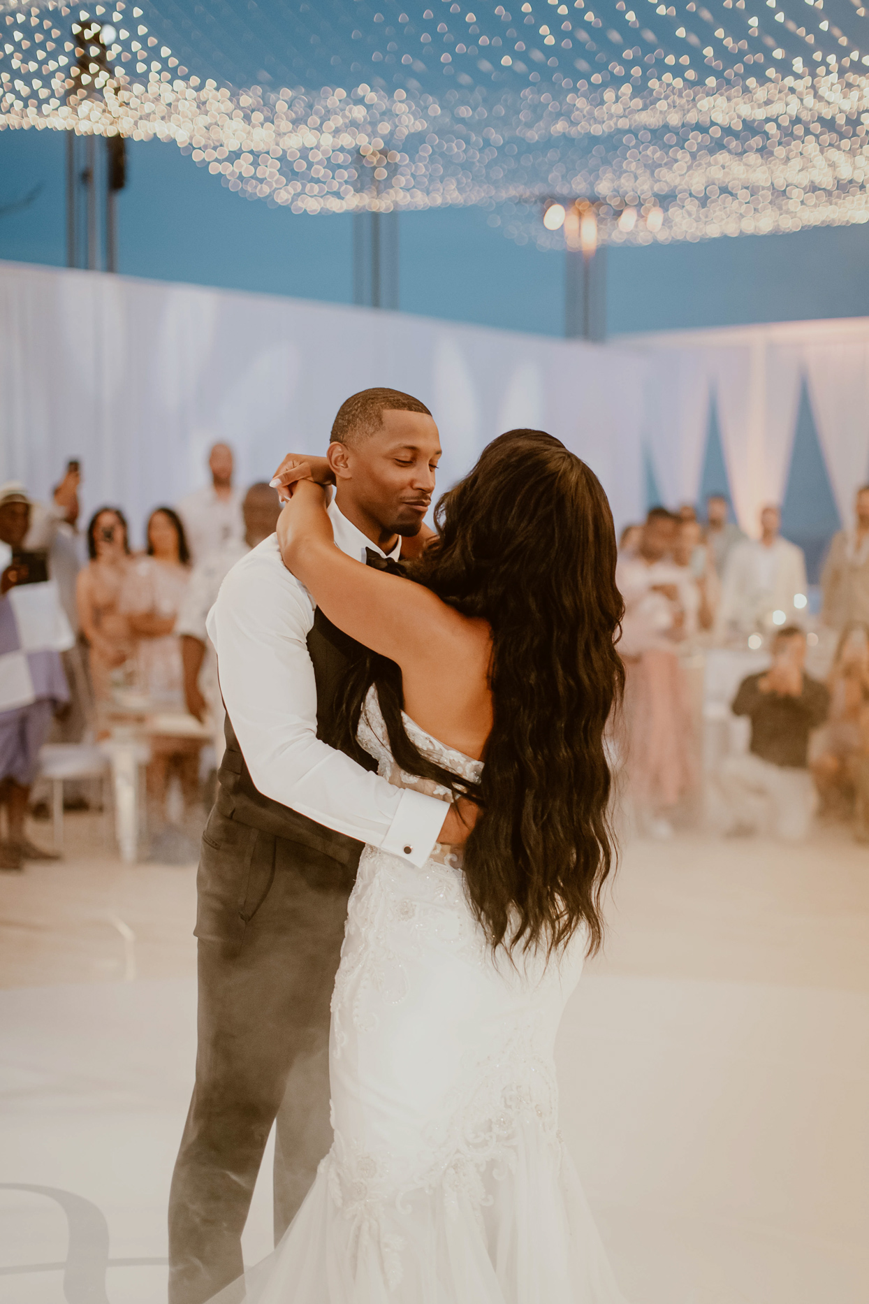 couple during first dance with blue sky and string lights behind