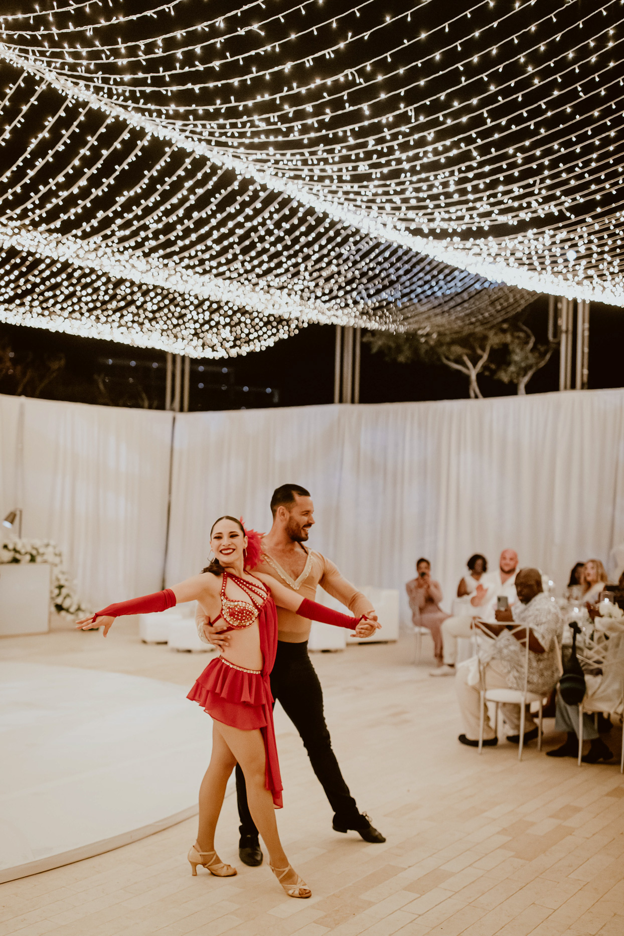 salsa dancers at reception with string lights above