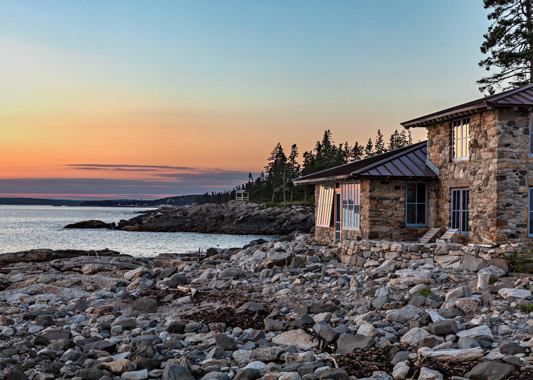 rustic main house on shoreline at sunset