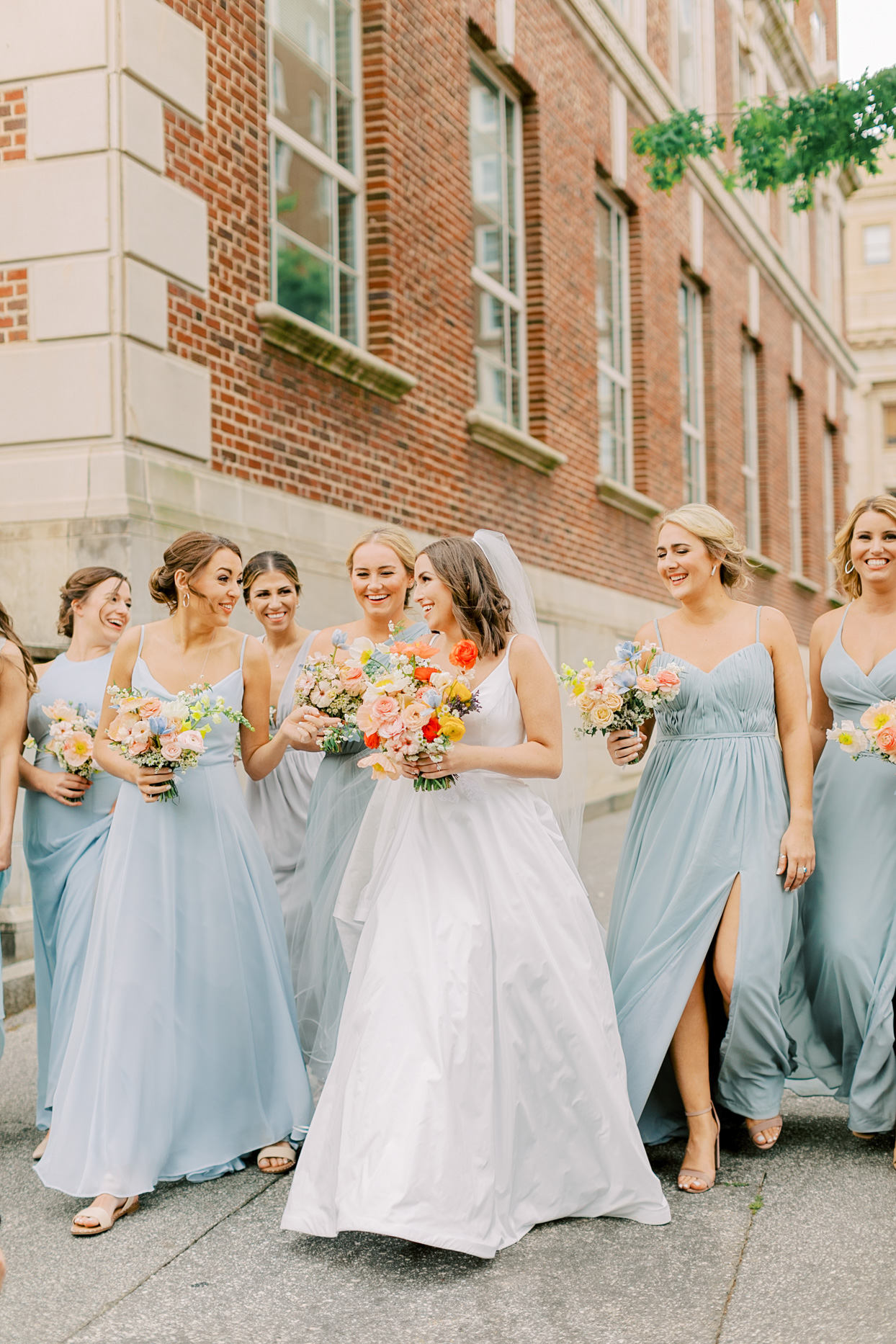 bride walking with bridesmaids wearing various styled pale blue dresses