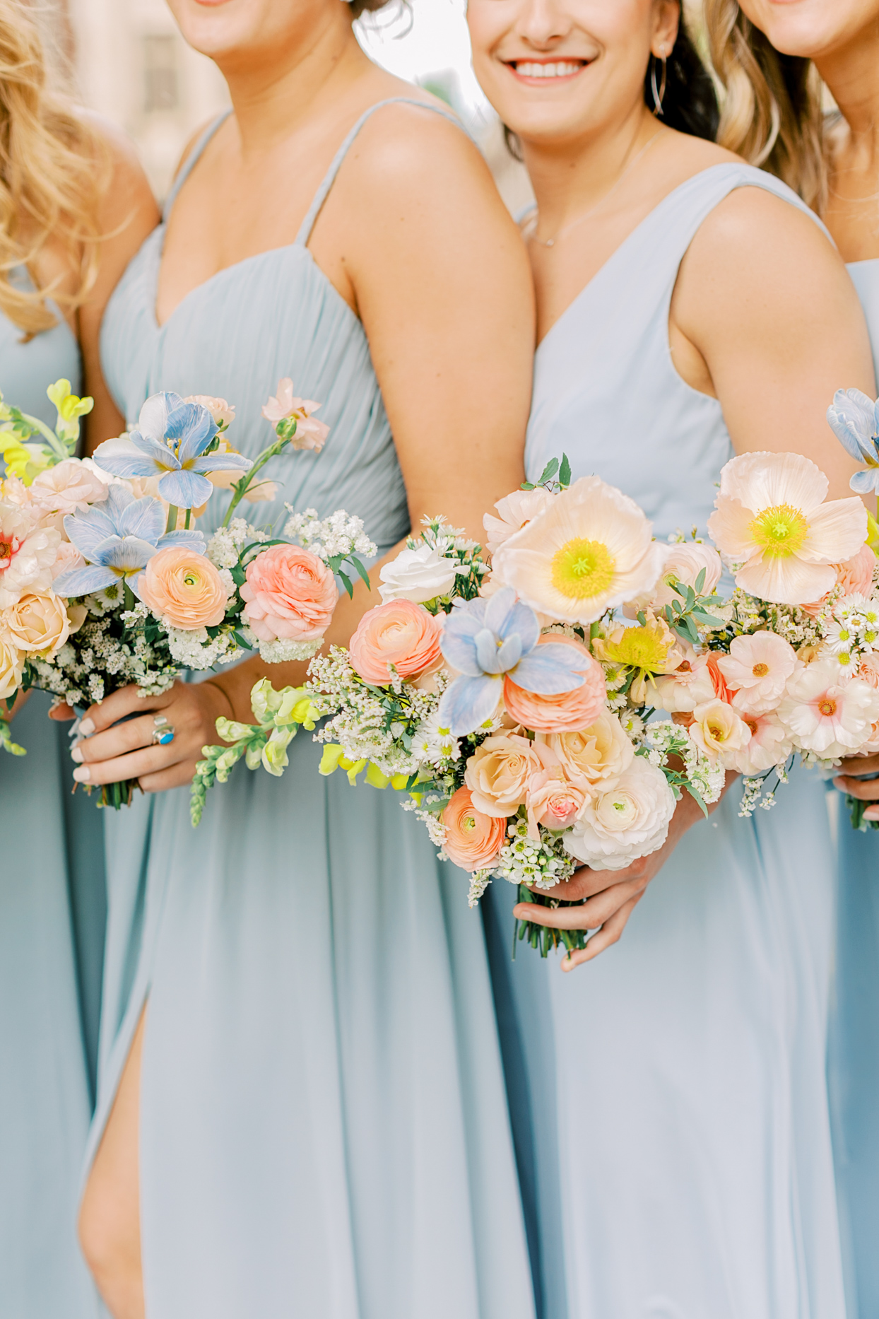bridesmaids wearing pale blue dresses holding spring hued floral bouquets