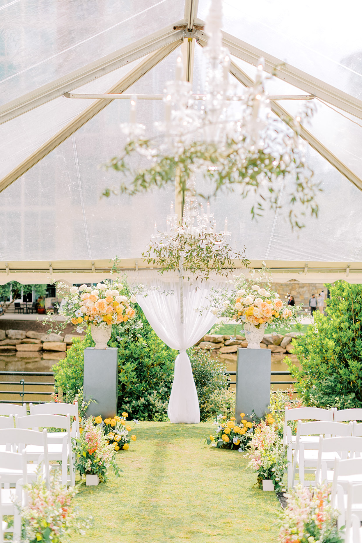 large white tent wedding ceremony space with various floral decor