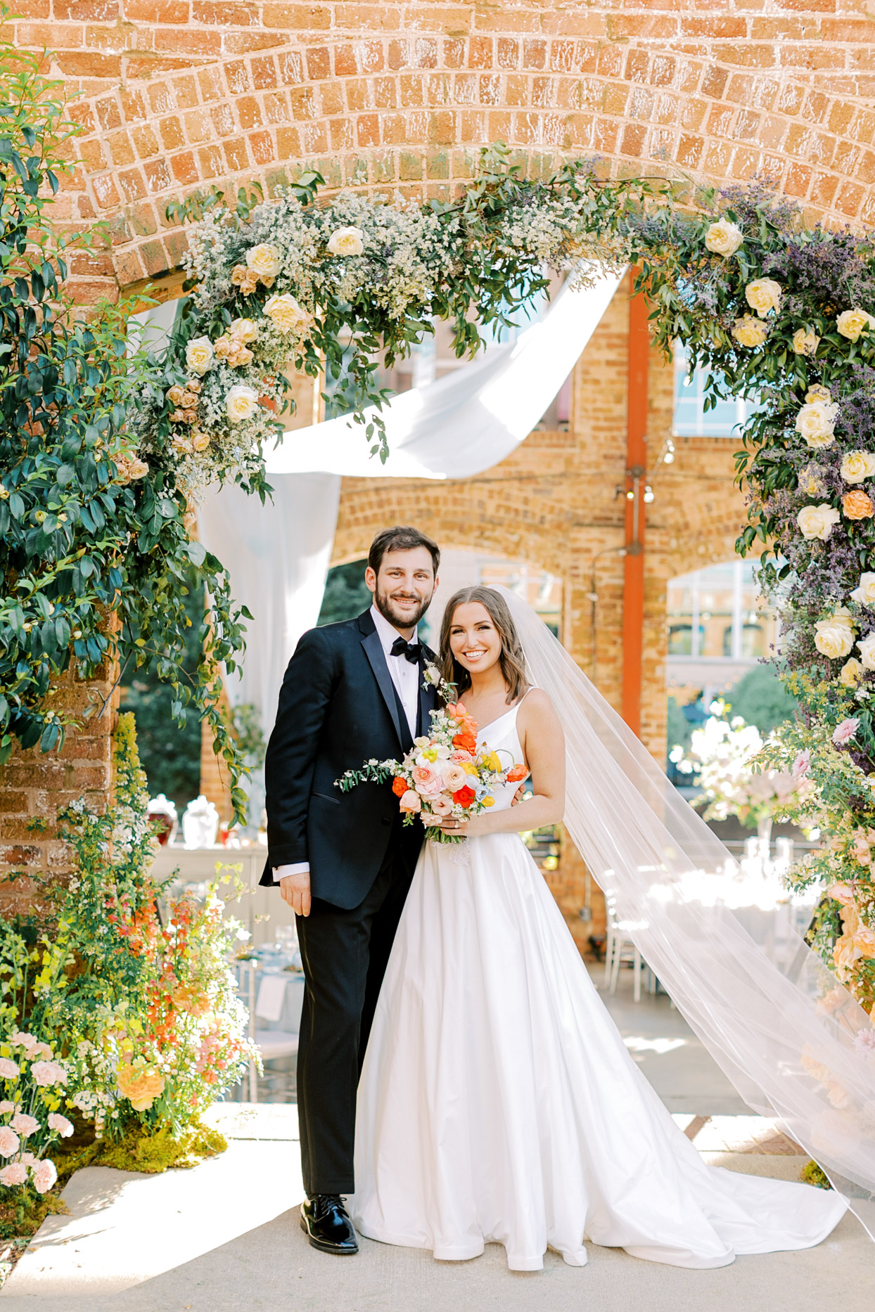 bride and groom smiling under floral covered archway
