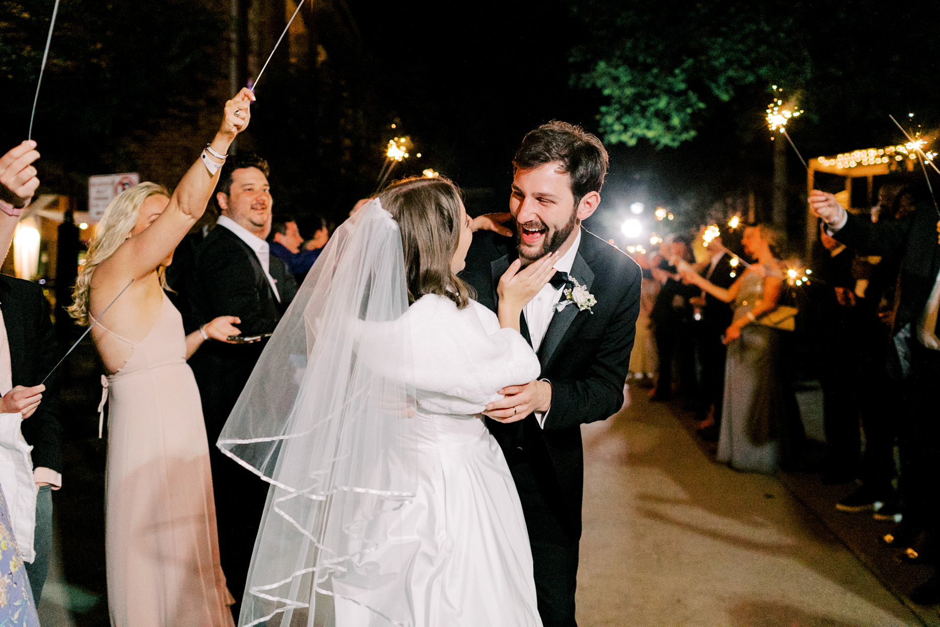 bride and groom smiling surrounded by guests with sparklers for wedding exit