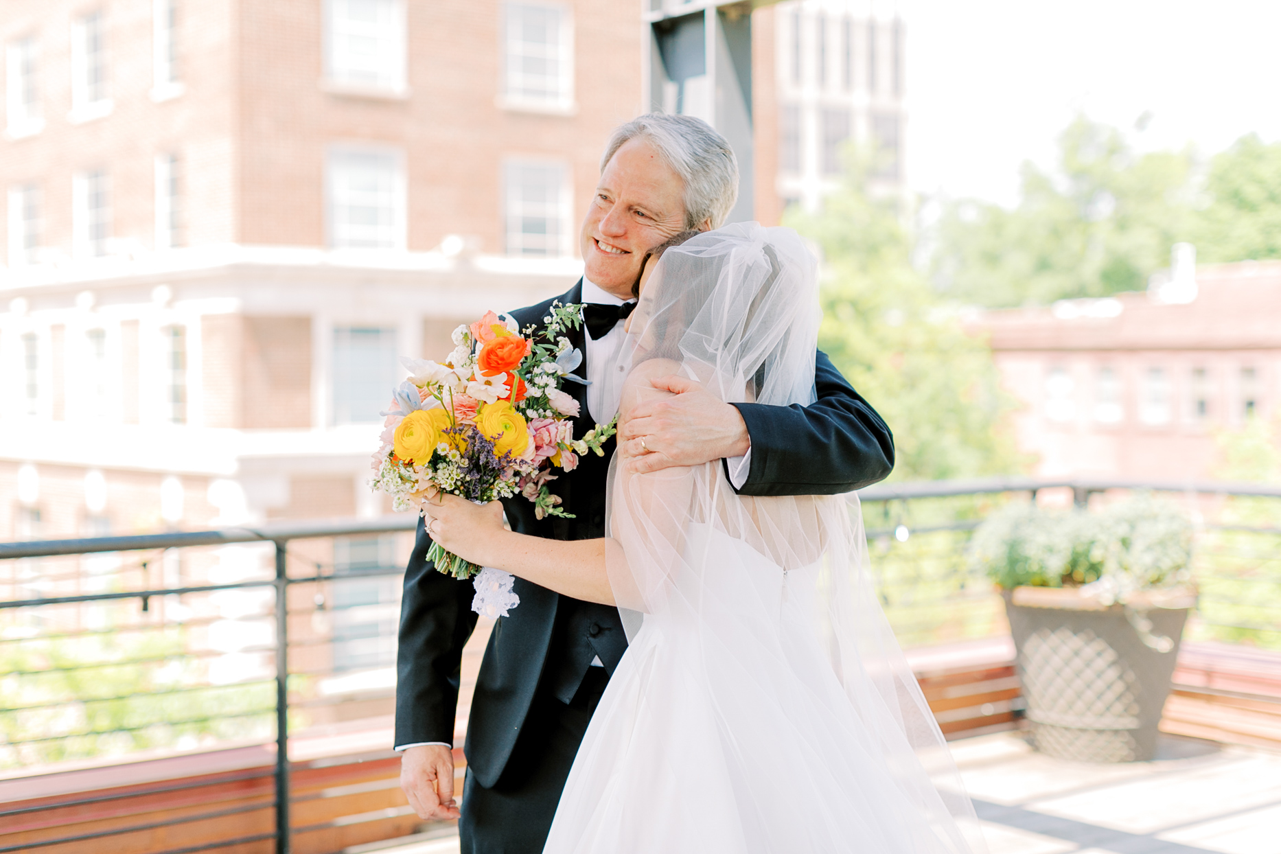 father of the bride hugging bride during first look
