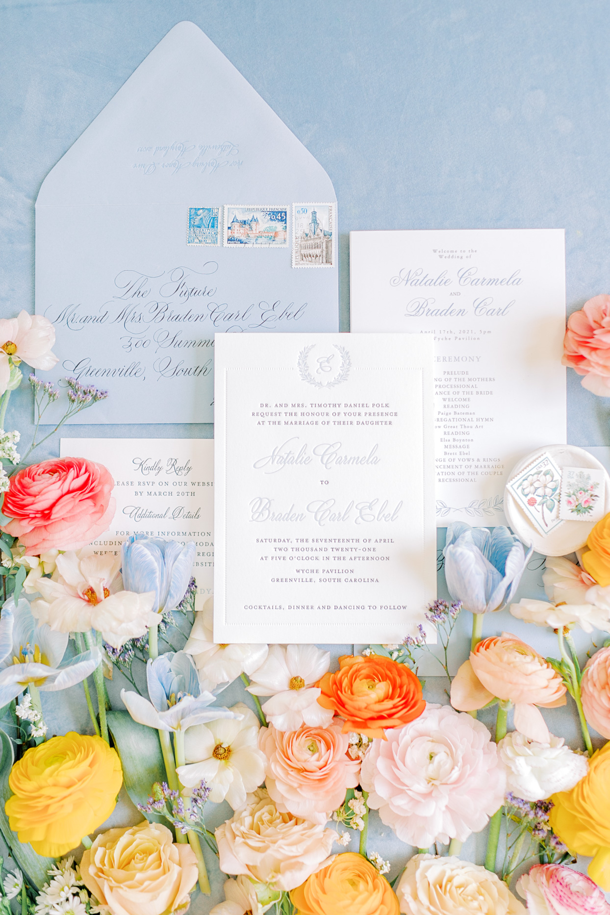 spring hued florals surrounding white and blue wedding stationery