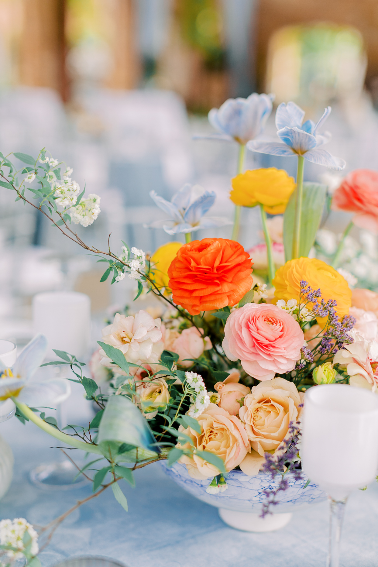 spring hued floral centerpieces in blue and white marble vase